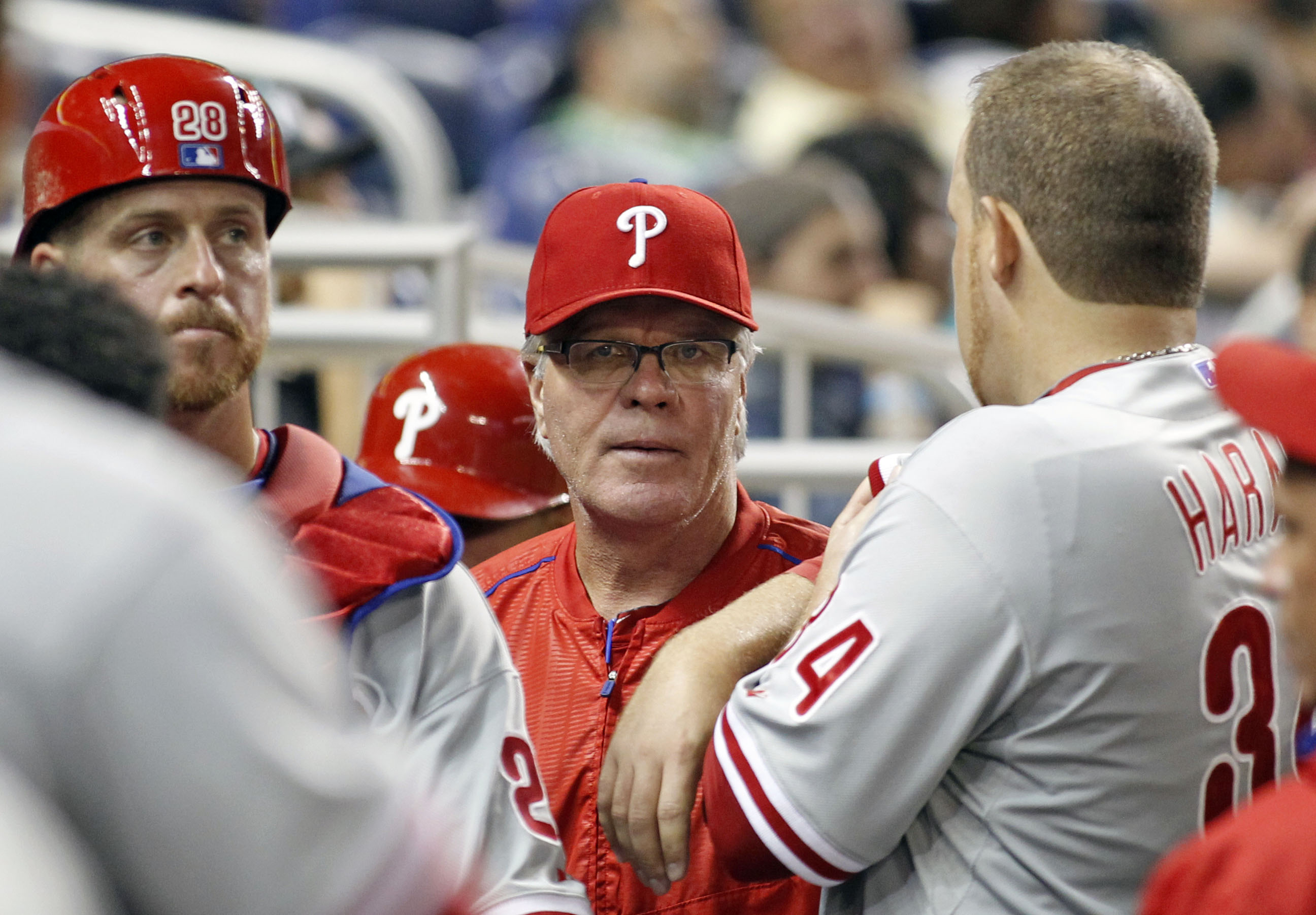 Philadelphia Phillies manager Pete Mackanin, center, speaks with starting pitcher Aaron Harang, right, and catcher Erik Kratz (28) in the third inning of play against the Miami Marlins during a baseball game in Miami, Tuesday, Sept. 22, 2015. (AP Photo/Jo