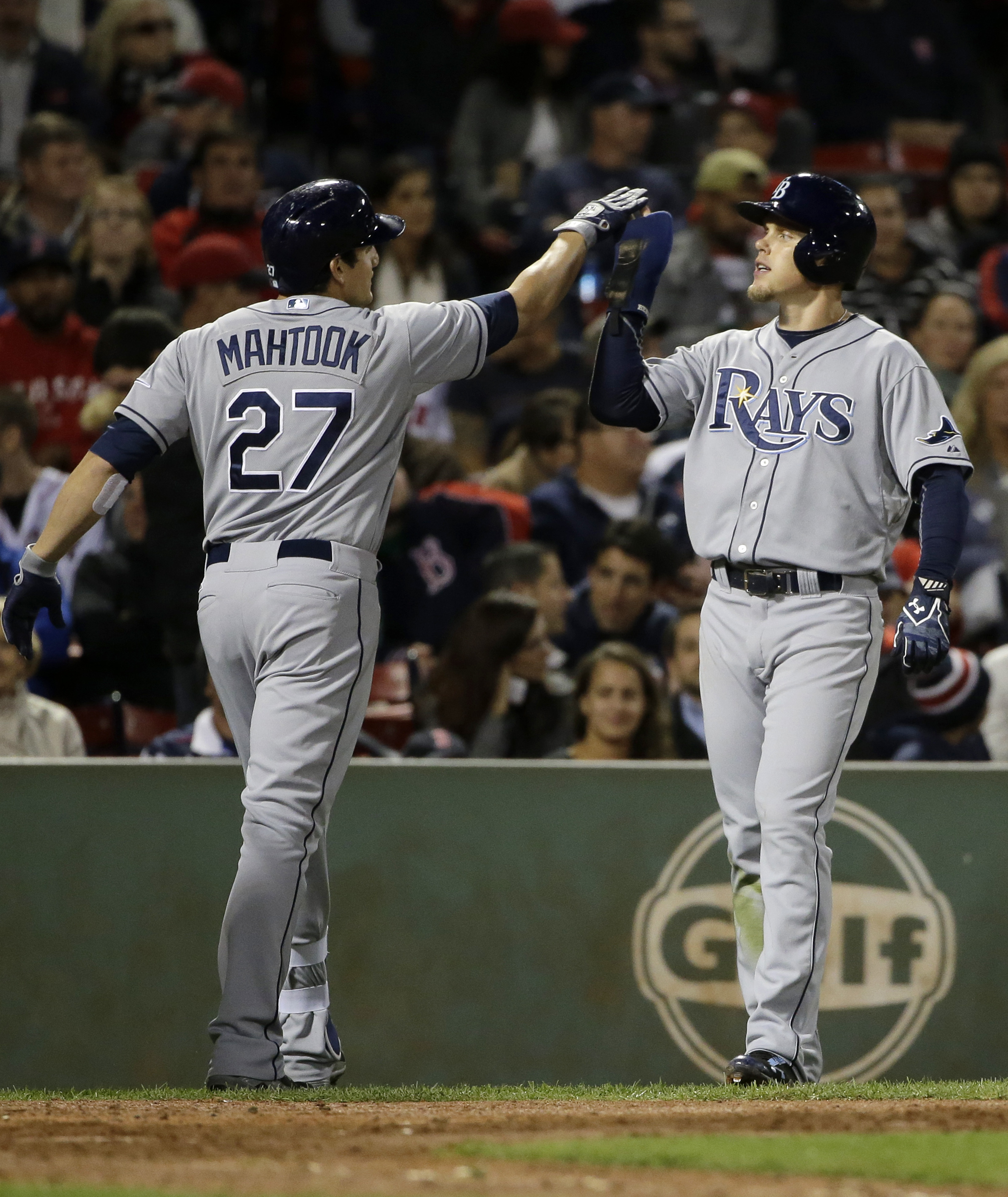 Tampa Bay Rays' Mikie Mahtook, left, celebrates with Brandon Guyer after Mahtook hit a two-run home run, allowing Guyer to score in the eighth inning of a baseball game against the Boston Red Sox, Tuesday, Sept. 22, 2015, in Boston. The Rays won 5-2. (AP