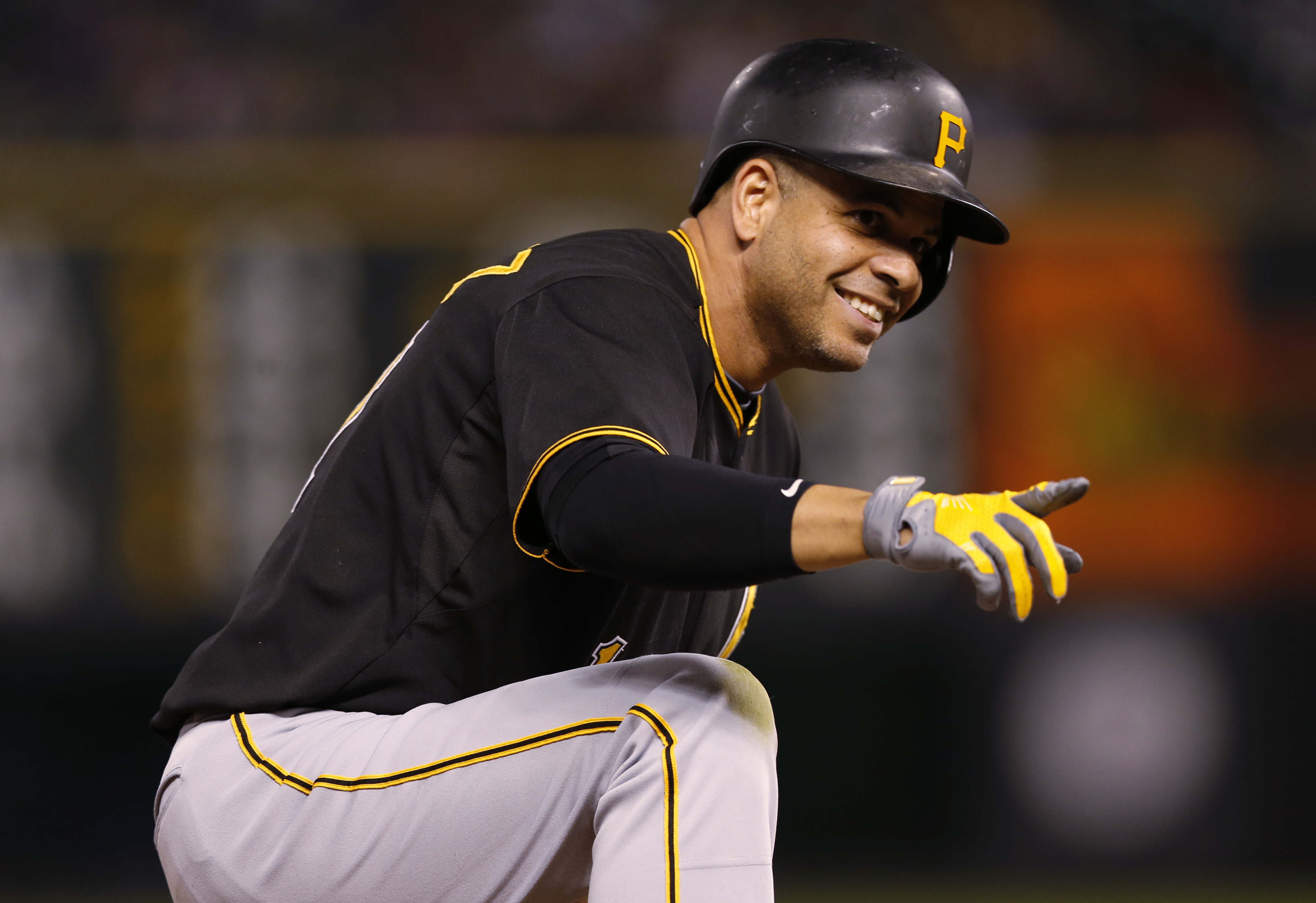Pittsburgh Pirates' Aramis Ramirez points to teammates after his RBI triple off Colorado Rockies starting pitcher Chris Rusin during the fourth inning of a baseball game Tuesday, Sept. 22, 2015, in Denver. (AP Photo/David Zalubowski)