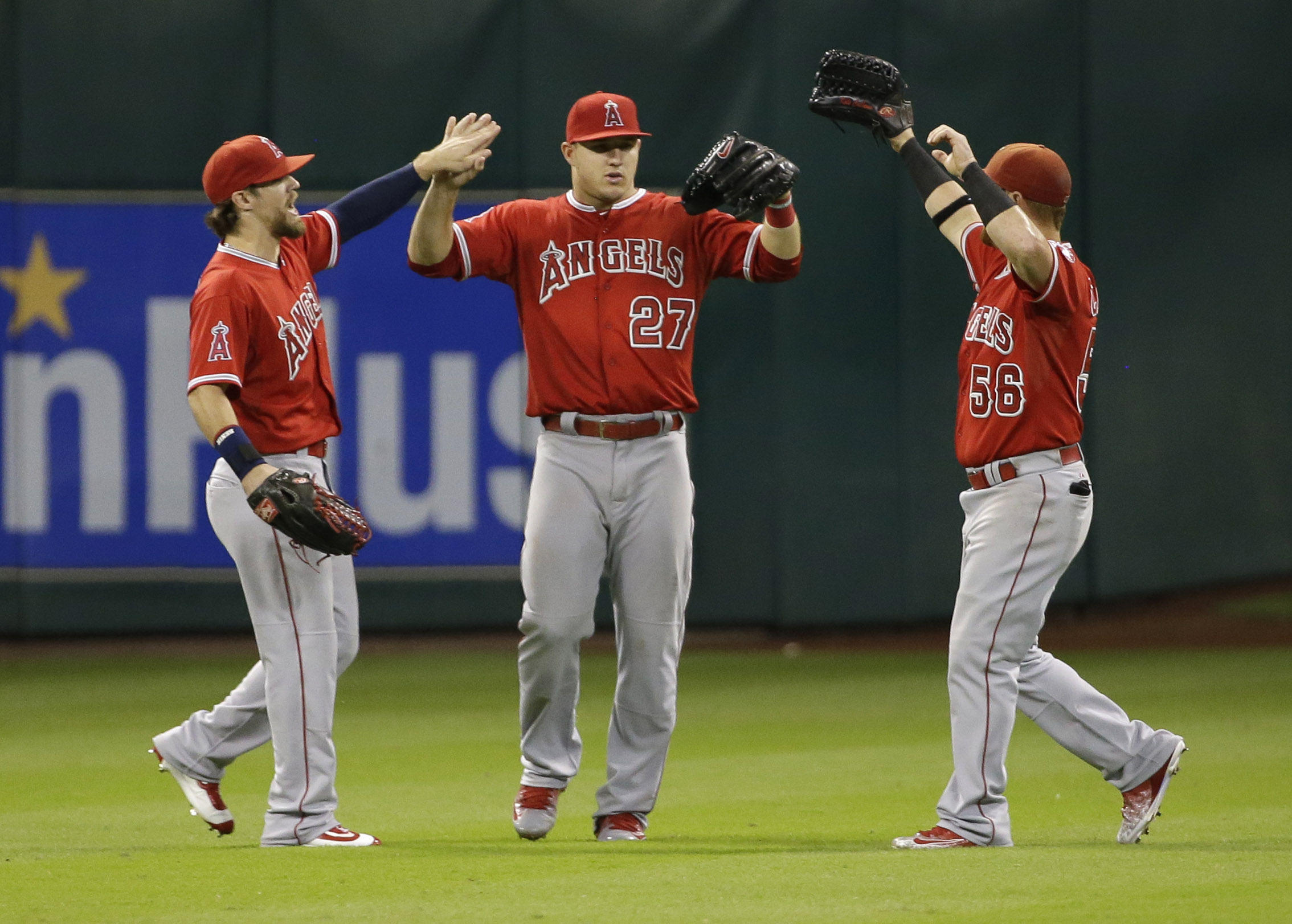 Los Angeles Angels' Collin Cowgill, left, Mike Trout (27) and Kole Calhoun (56) celebrate after the Angels defeated the Houston Astros 4-3 in a baseball game Tuesday, Sept. 22, 2015, in Houston. (AP Photo/David J. Phillip)