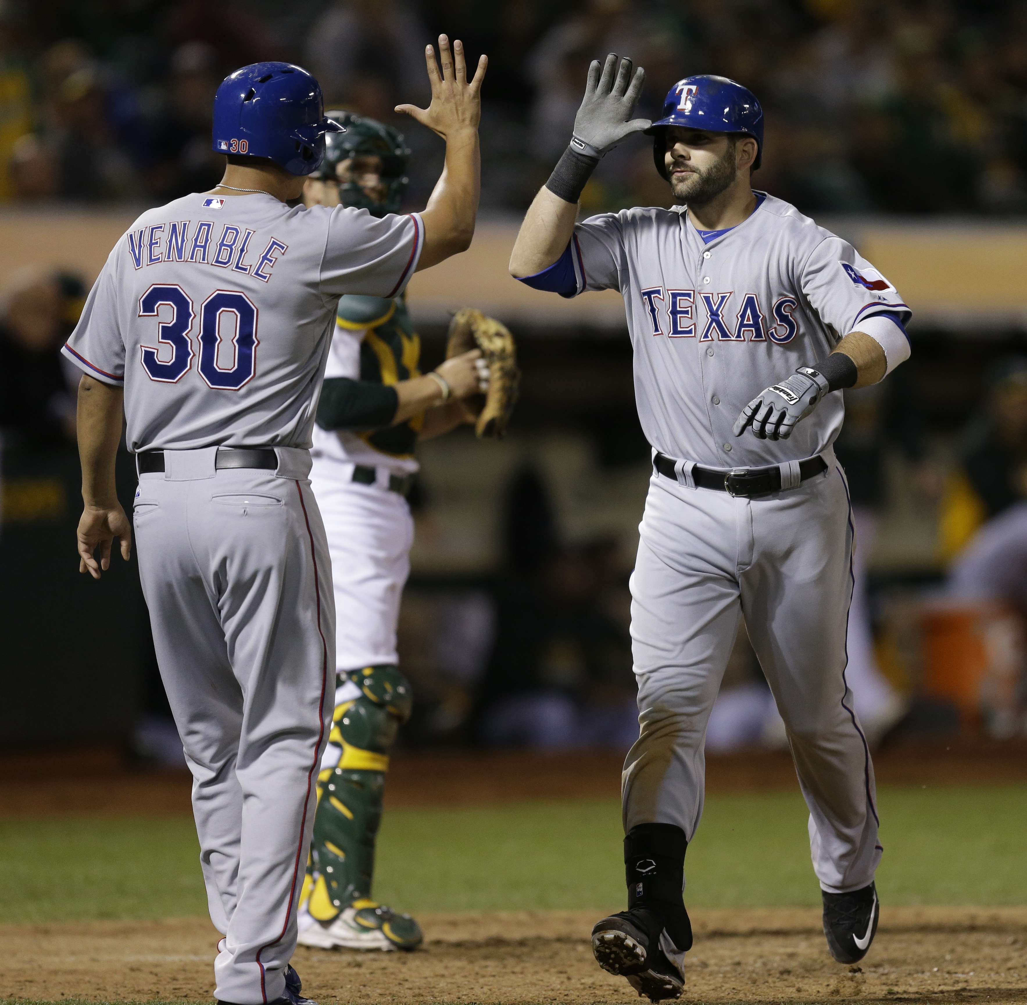 Texas Rangers' Mitch Moreland, right, is congratulated by Will Venable (30) after hitting a two-run home run off Oakland Athletics' Sean Nolin during the sixth inning of a baseball game Tuesday, Sept. 22, 2015, in Oakland, Calif. (AP Photo/Ben Margot)