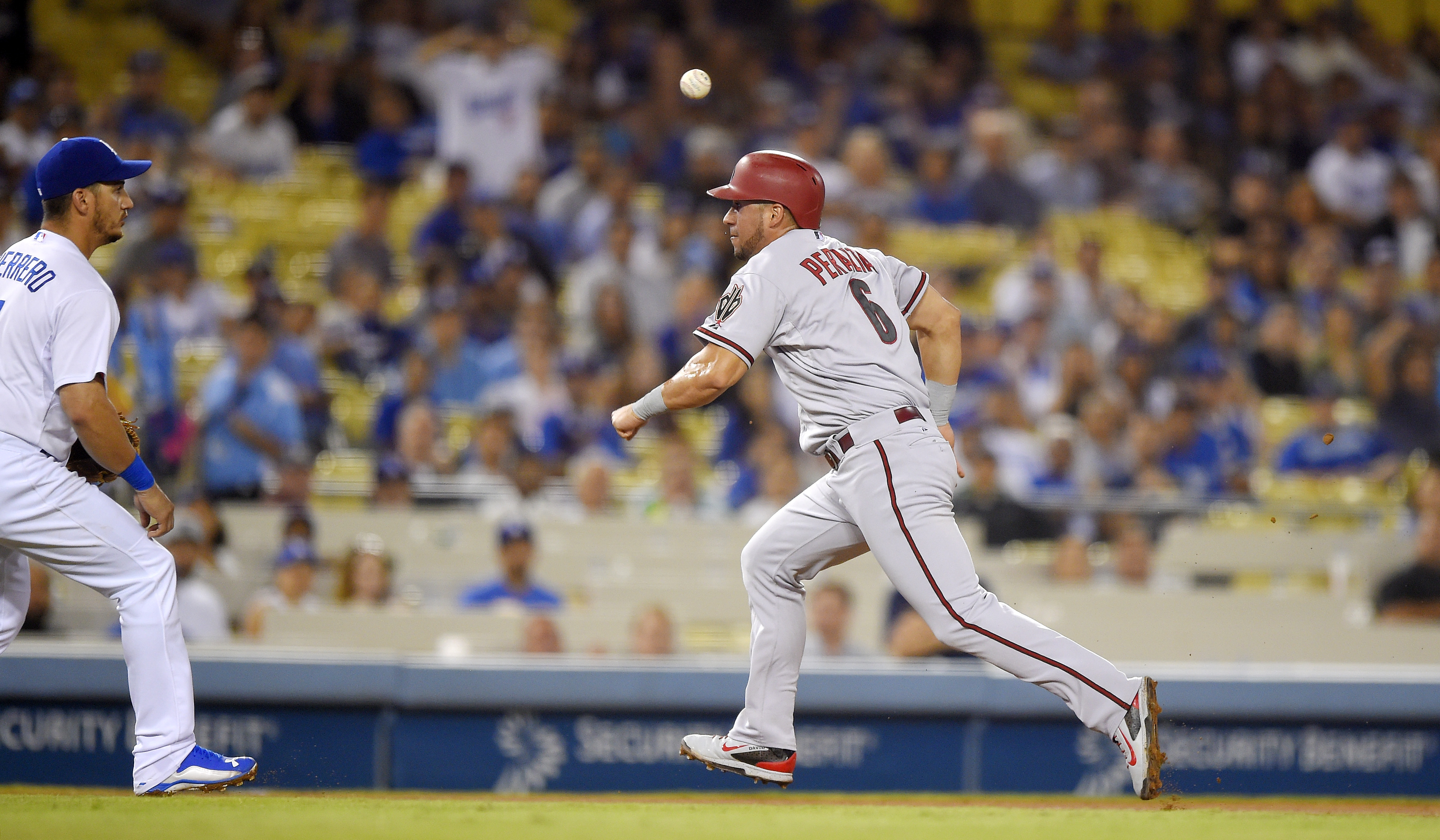 A ball sails over Arizona Diamondbacks' David Peralta, right, as he is caught between second an third while Los Angeles Dodgers left fielder Alex Guerrero watches during the eighth inning of a baseball game, Tuesday, Sept. 22, 2015, in Los Angeles. Peralt