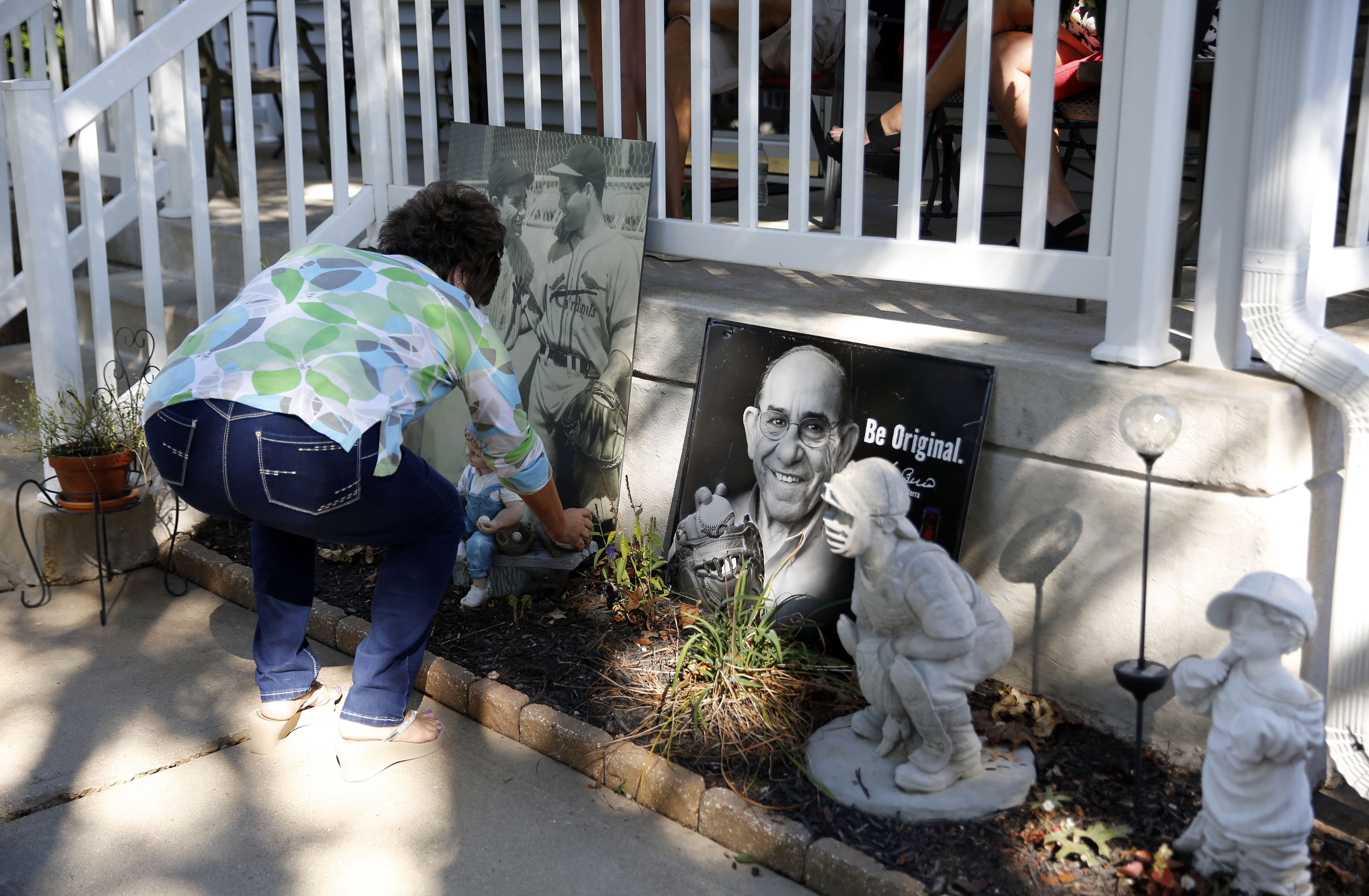 Barbara Berra places a baseball at a memorial outside the boyhood home of her uncle, baseball Hall of Fame catcher Yogi Berra, Wednesday, Sept. 23, 2015, in St. Louis. Berra, who helped the New York Yankees to 10 World Series championships has died Tuesda