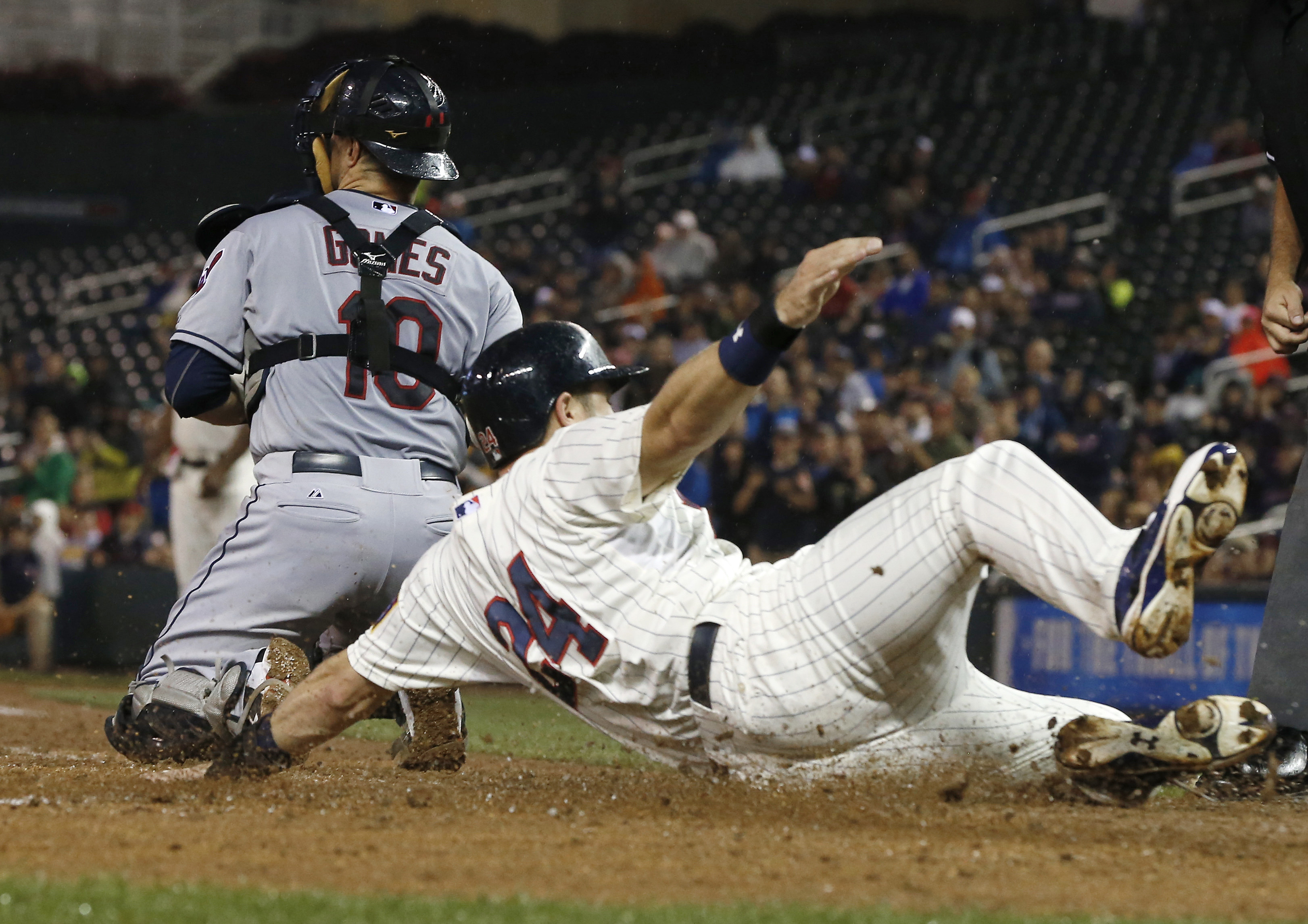 Minnesota Twins' Trevor Plouffe scores behind Cleveland Indians catcher Yan Gomes on a two-run single by Eduardo Escobar off Indians pitcher Corey Kluber in the fourth inning of a baseball game, Wednesday, Sept. 23, 2015, in Minneapolis. (AP Photo/Jim Mon