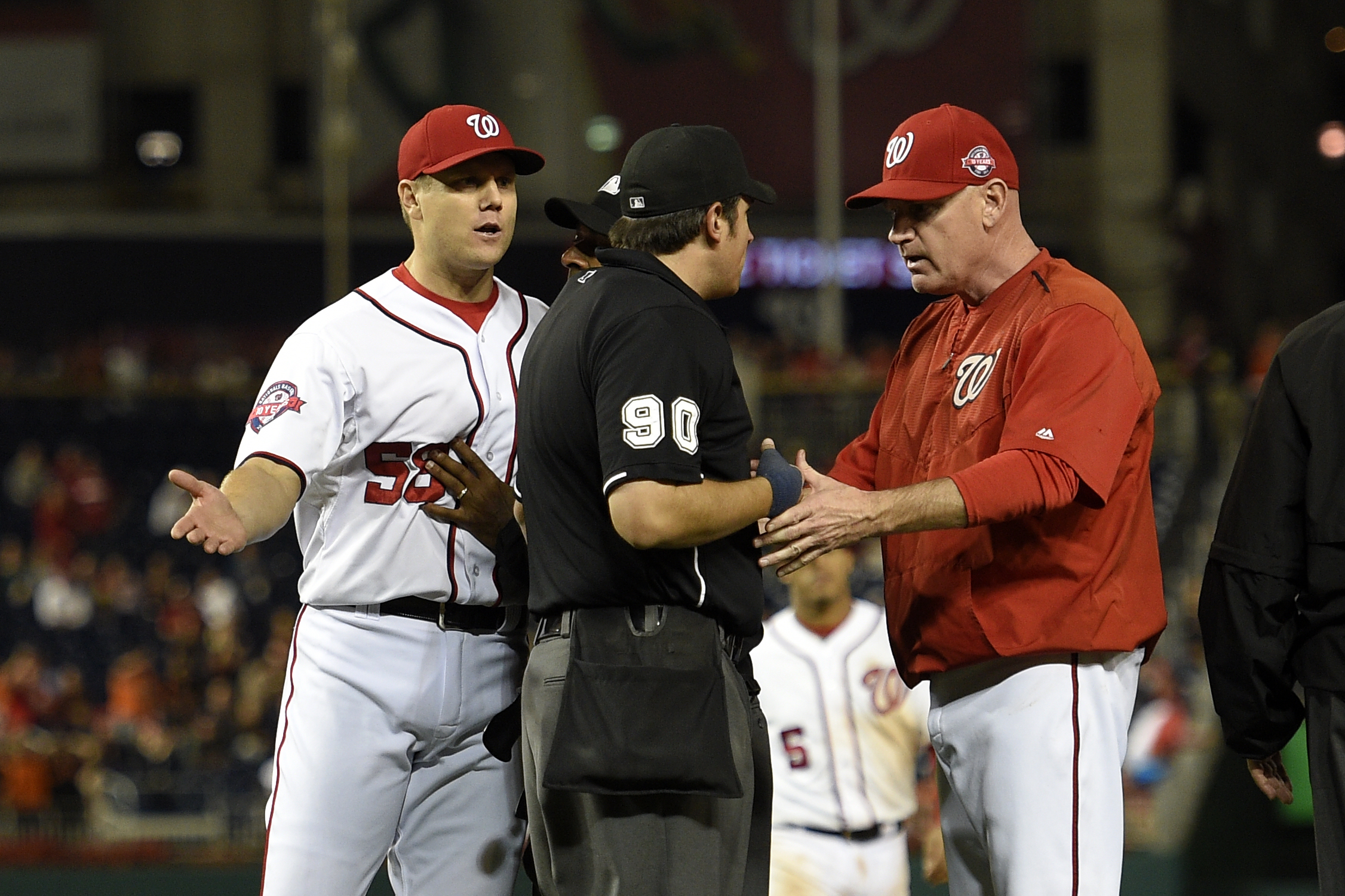 Washington Nationals relief pitcher Jonathan Papelbon, left, reacts as manager Matt Williams , right, talks with home plate umpire Mark Ripperger (90) during the ninth inning of an interleague baseball game, Wednesday, Sept. 23, 2015, in Washington. Papel