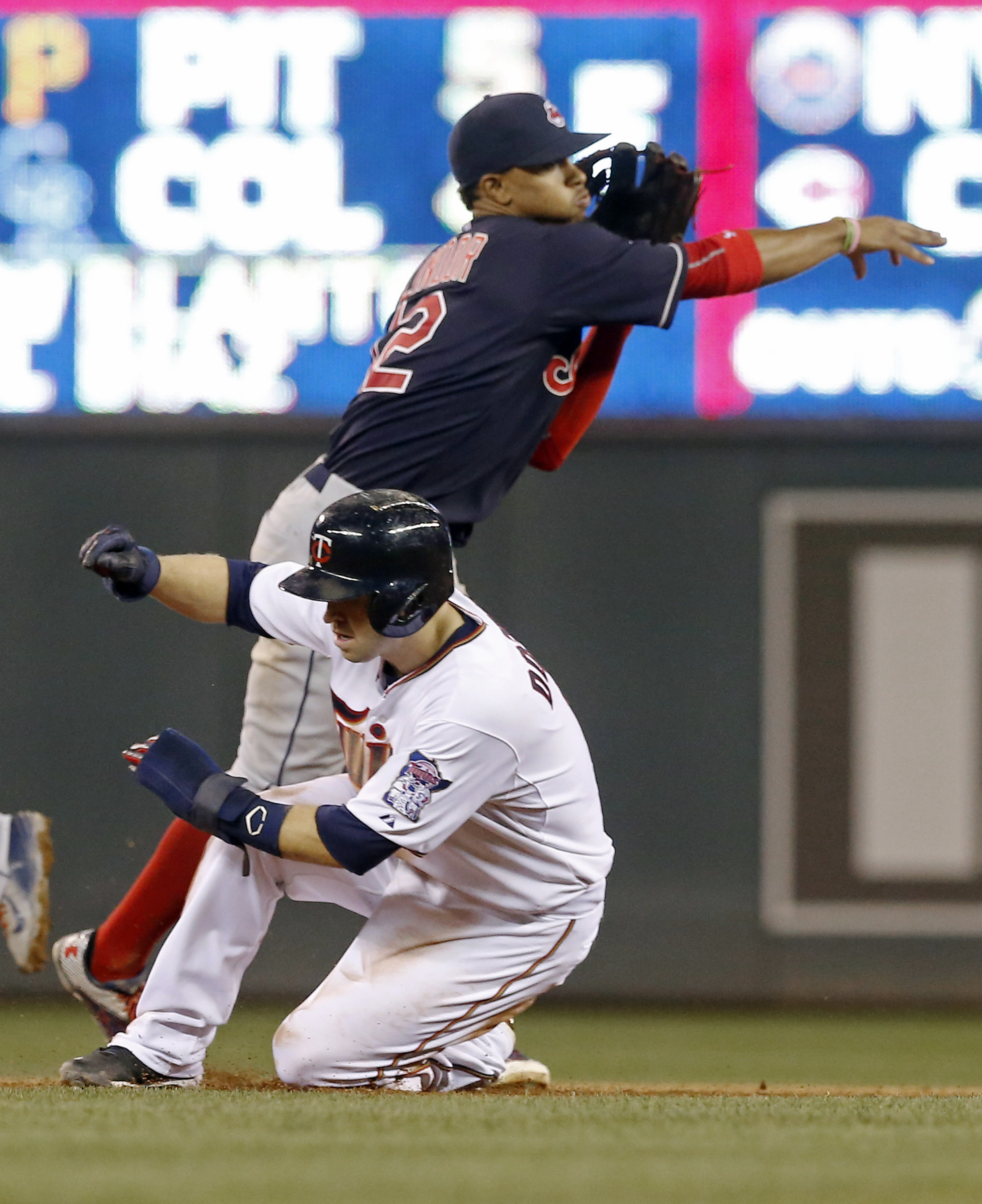 Cleveland Indians shortstop Francisco Lindor, right, completes the double play after the force at second of Minnesota Twins' Brian Dozier in the sixth inning of a baseball game, Thursday, Sept. 24, 2015, in Minneapolis. Twins' Joe Mauer hit into the doubl