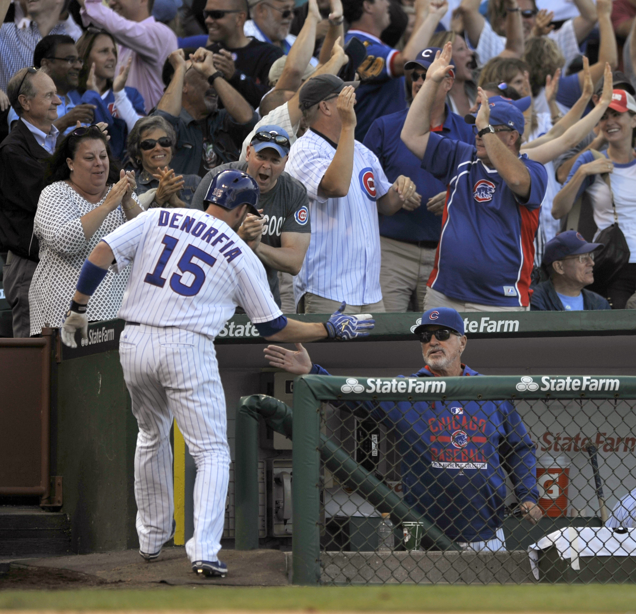 Chicago Cubs' Chris Denorfia (15 celebrates with manager Joe Maddon in the dugout after scoring on a Starlin Castro triple during the ninth inning of a baseball game against the Pittsburgh Pirates Friday, Sept. 25, 2015 in Chicago. Pittsburgh won 3-2. (AP