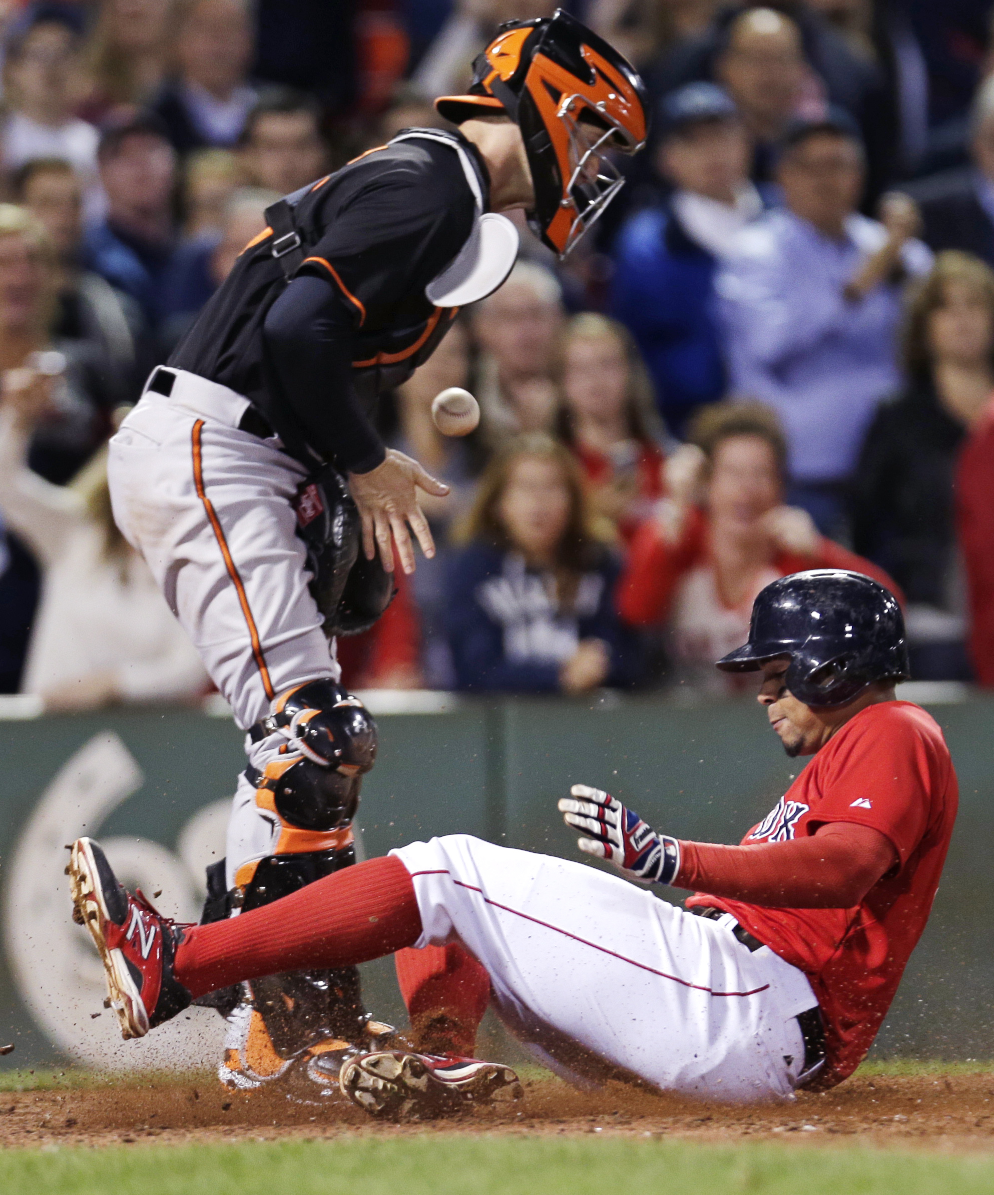 Baltimore Orioles catcher Caleb Joseph loses control of the ball as Boston Red Sox's Xander Bogaerts, right, scores on a double by David Ortiz during the eighth inning of a baseball game at Fenway Park in Boston, Friday, Sept. 25, 2015. (AP Photo/Charles