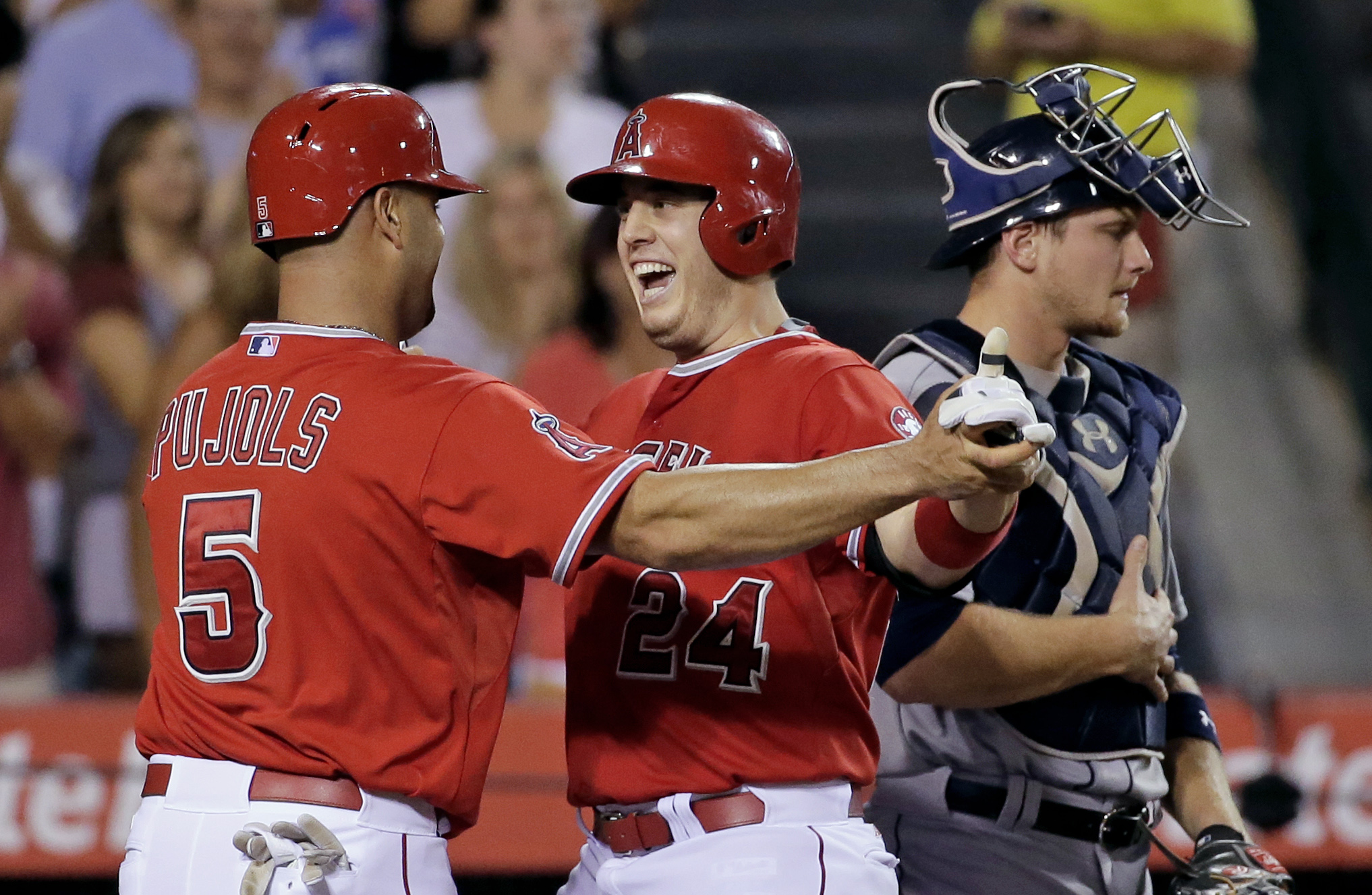 Los Angeles Angels' C.J. Cron, middle, celebrates after his two-run home run past Seattle Mariners catcher John Hicks, right, with Albert Pujols during the seventh inning of a baseball game in Anaheim, Calif., Friday, Sept. 25, 2015. (AP Photo/Chris Carls