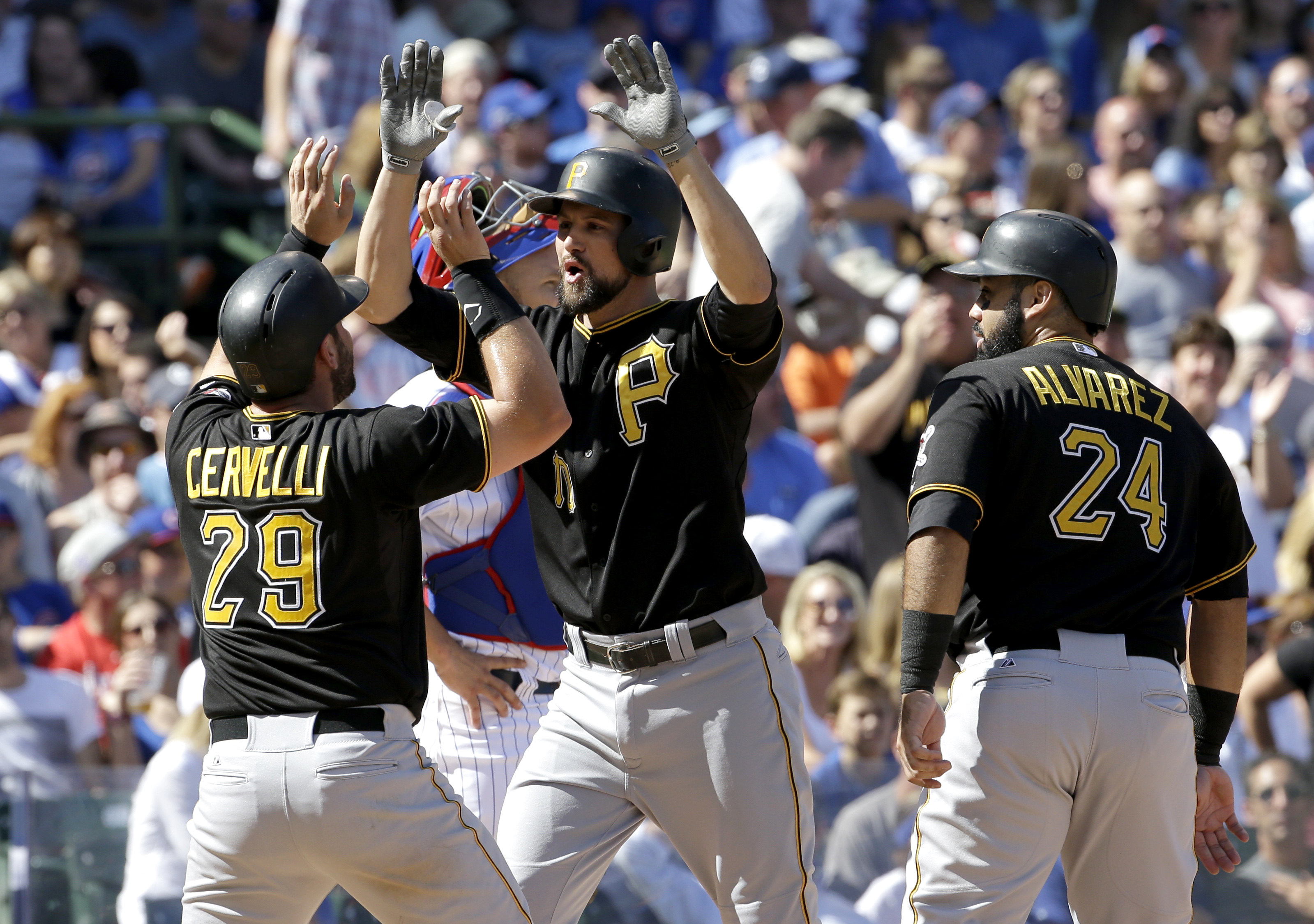 Pittsburgh Pirates' Jordy Mercer, center, celebrates with Francisco Cervelli, left, and Pedro Alvarez after hitting a three-run home run during the fifth inning of a baseball game against the Chicago Cubs, Saturday, Sept. 26, 2015, in Chicago. (AP Photo/N