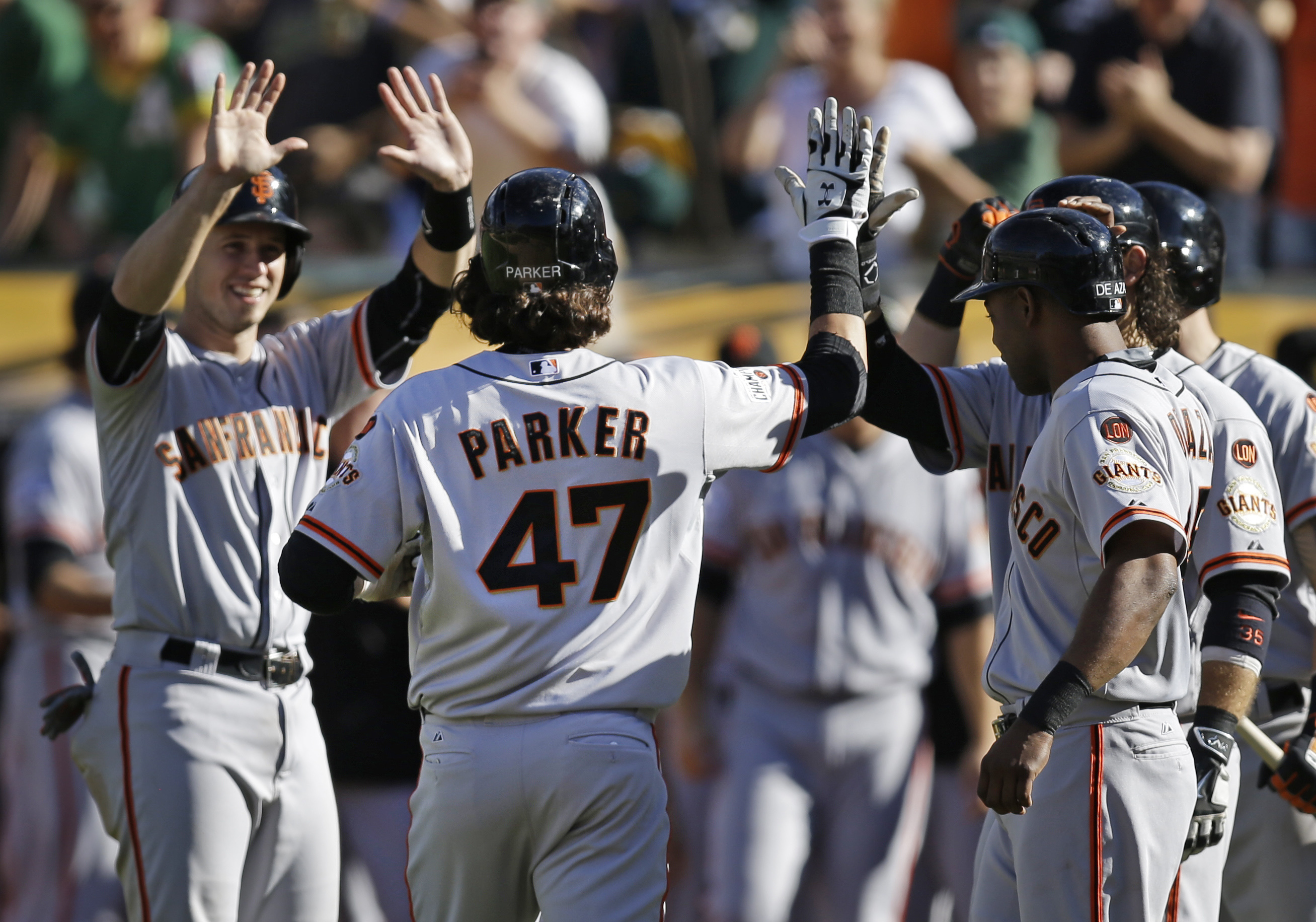 San Francisco Giants' Jarrett Parker (47) is congratulated by teammates after hitting a grand slam off Oakland Athletics' Ryan Dull in the eighth inning of a baseball game Saturday, Sept. 26, 2015, in Oakland, Calif. (AP Photo/Ben Margot)