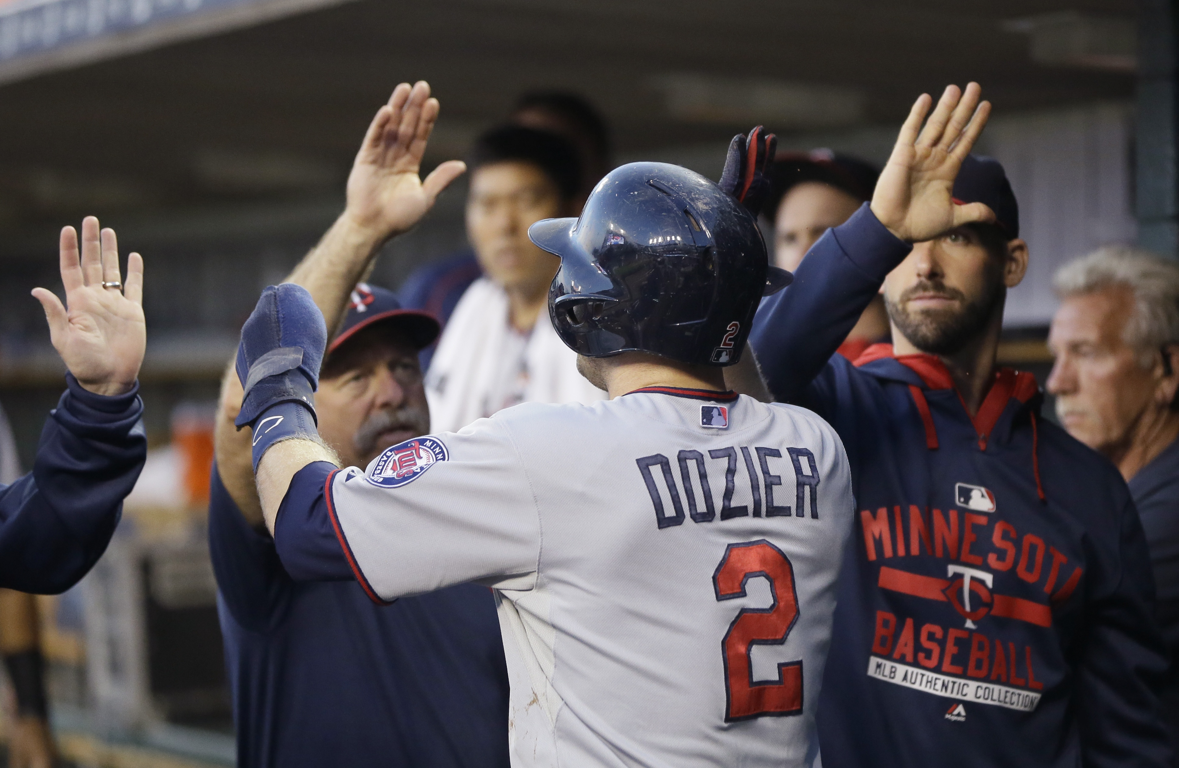 Minnesota Twins' Brian Dozier is congratulated after scoring during the first inning of a baseball game against the Detroit Tigers, Saturday, Sept. 26, 2015 in Detroit. (AP Photo/Carlos Osorio)