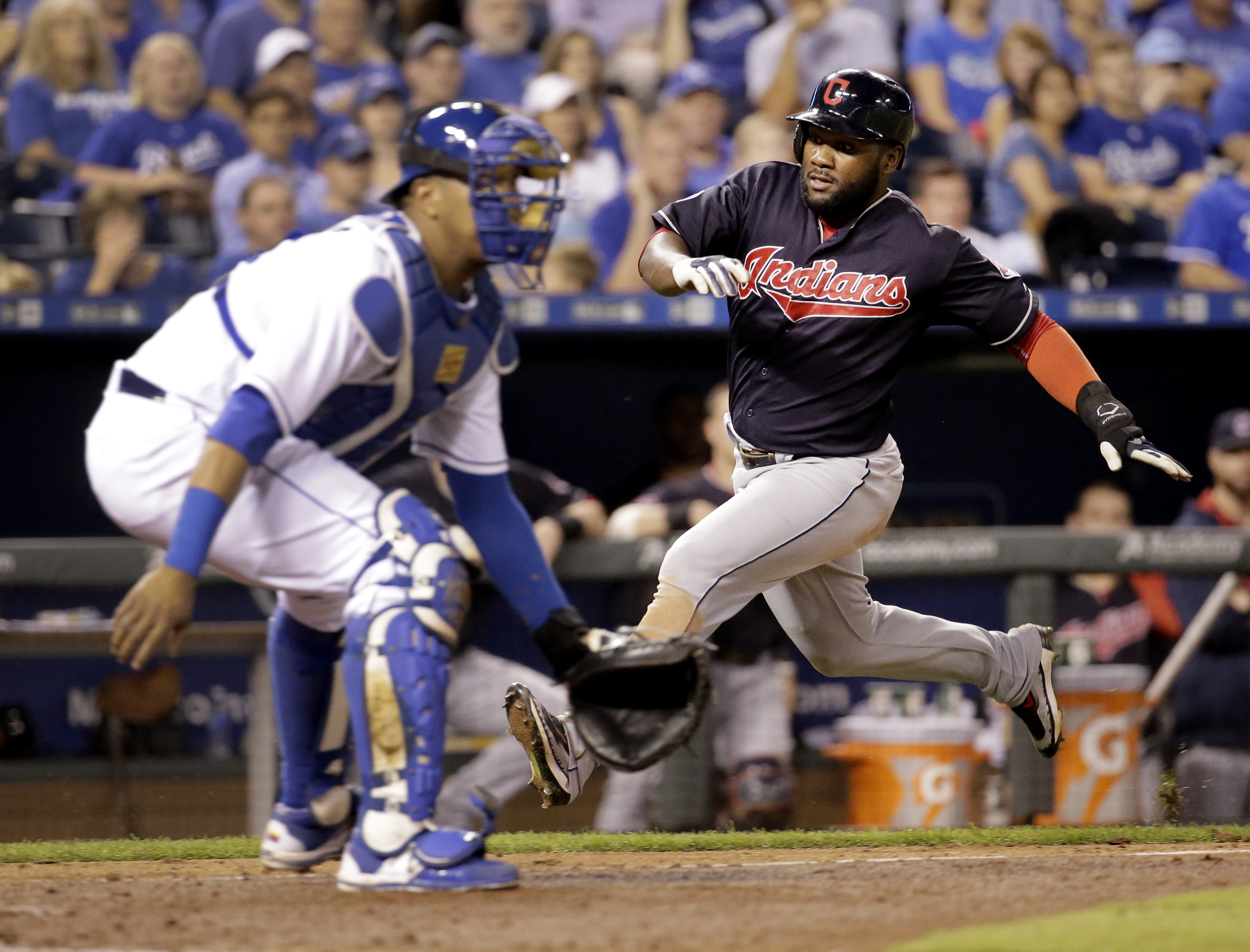 Cleveland Indians' Abraham Almonte runs past Kansas City Royals catcher Salvador Perez to score on a single by Jason Kipnis during the sixth inning of a baseball game Saturday, Sept. 26, 2015, in Kansas City, Mo. (AP Photo/Charlie Riedel)