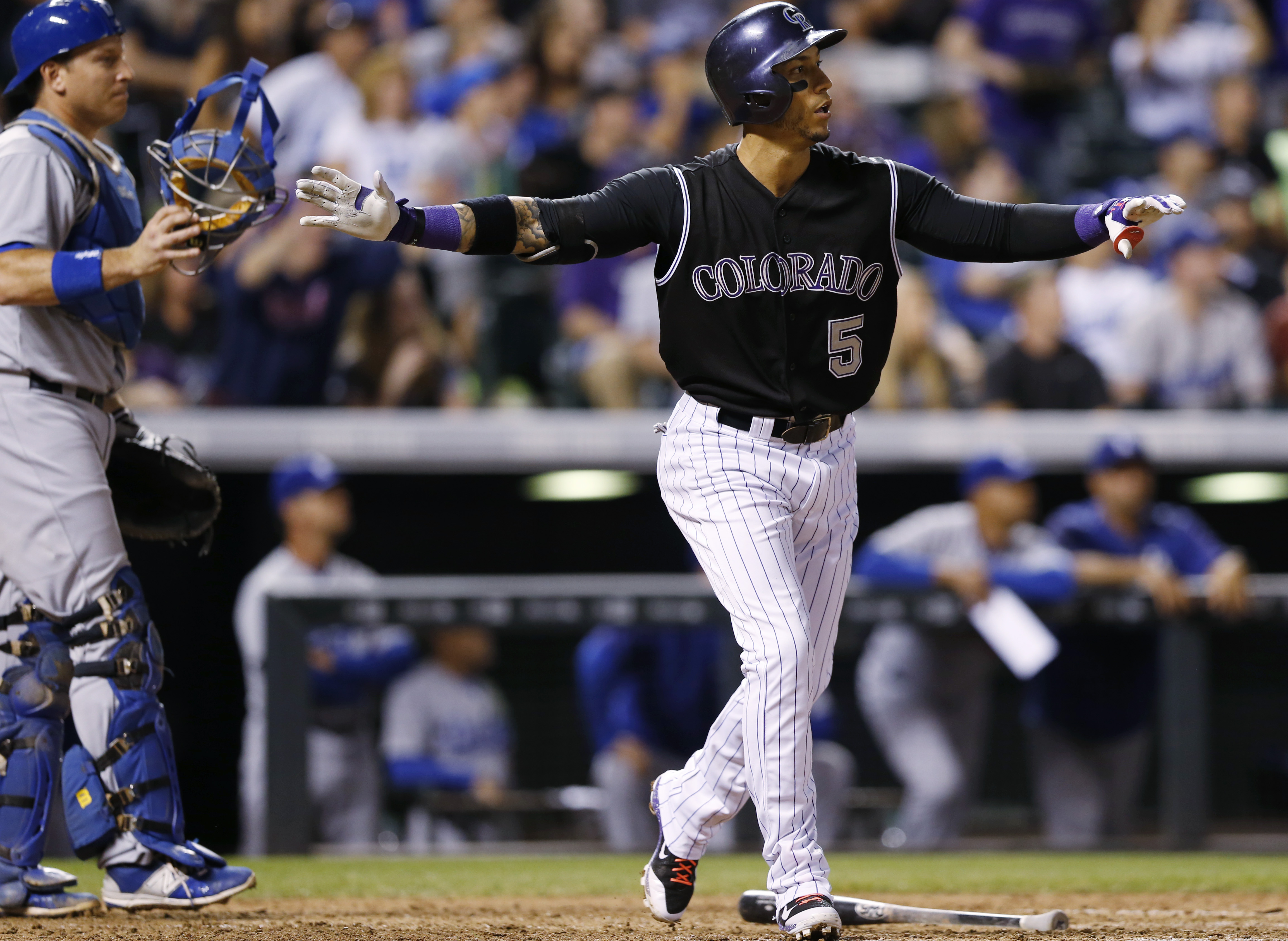 Colorado Rockies' Carlos Gonzalez, right, reacts after hitting a walkoff home run as Los Angeles Dodgers catcher A.J. Ellis looks on in the ninth inning of a baseball game Saturday, Sept. 26, 2015, in Denver. The Rockies won 8-6. (AP Photo/David Zalubowsk
