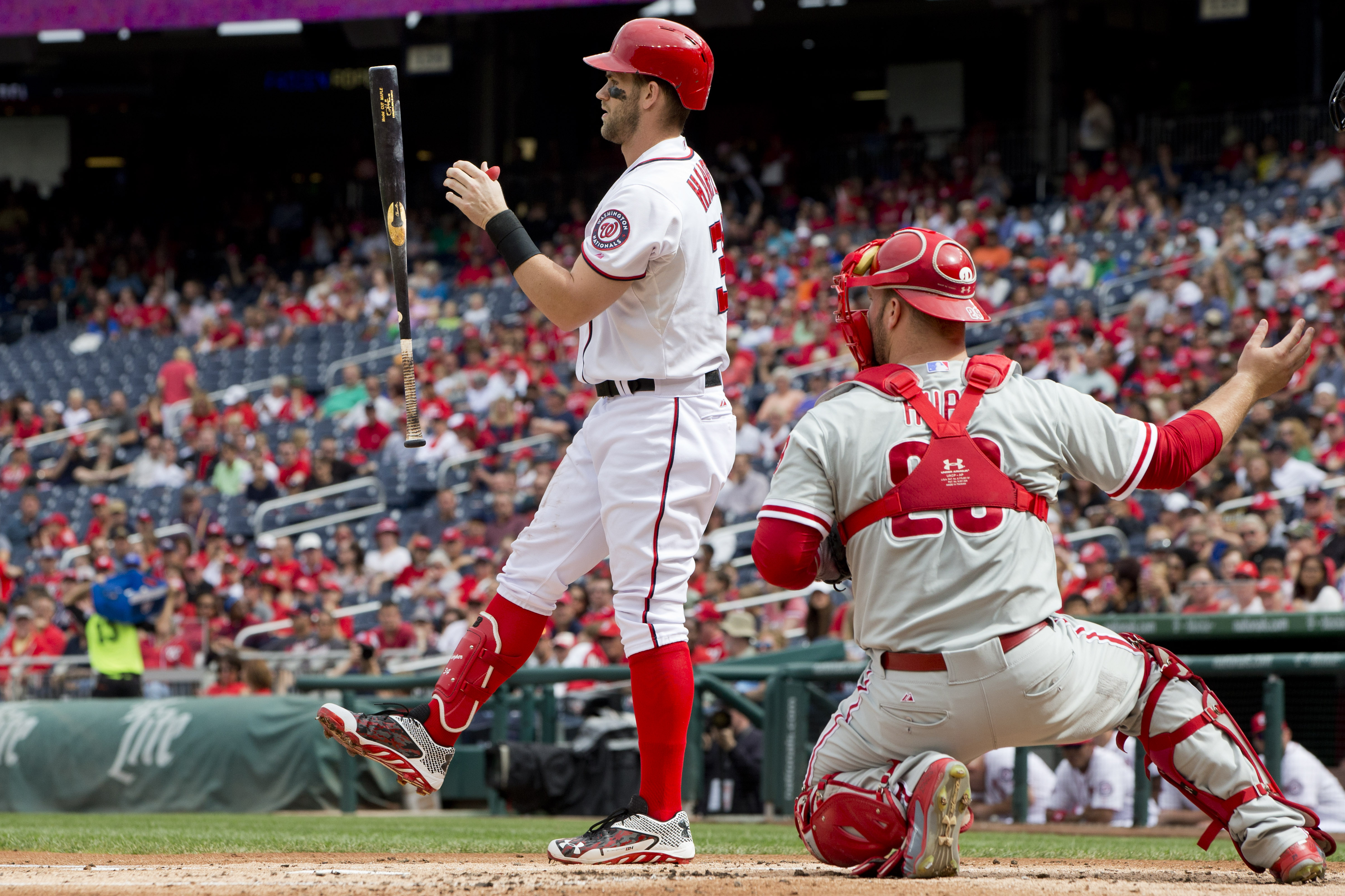 Washington Nationals' Bryce Harper (34) flips his bat in the air while batting in the first inning of a baseball game against the Philadelphia Phillies at Nationals Park, in Washington, on Sunday, Sept. 27, 2015, next to Phillies catcher Erik Kratz (28).