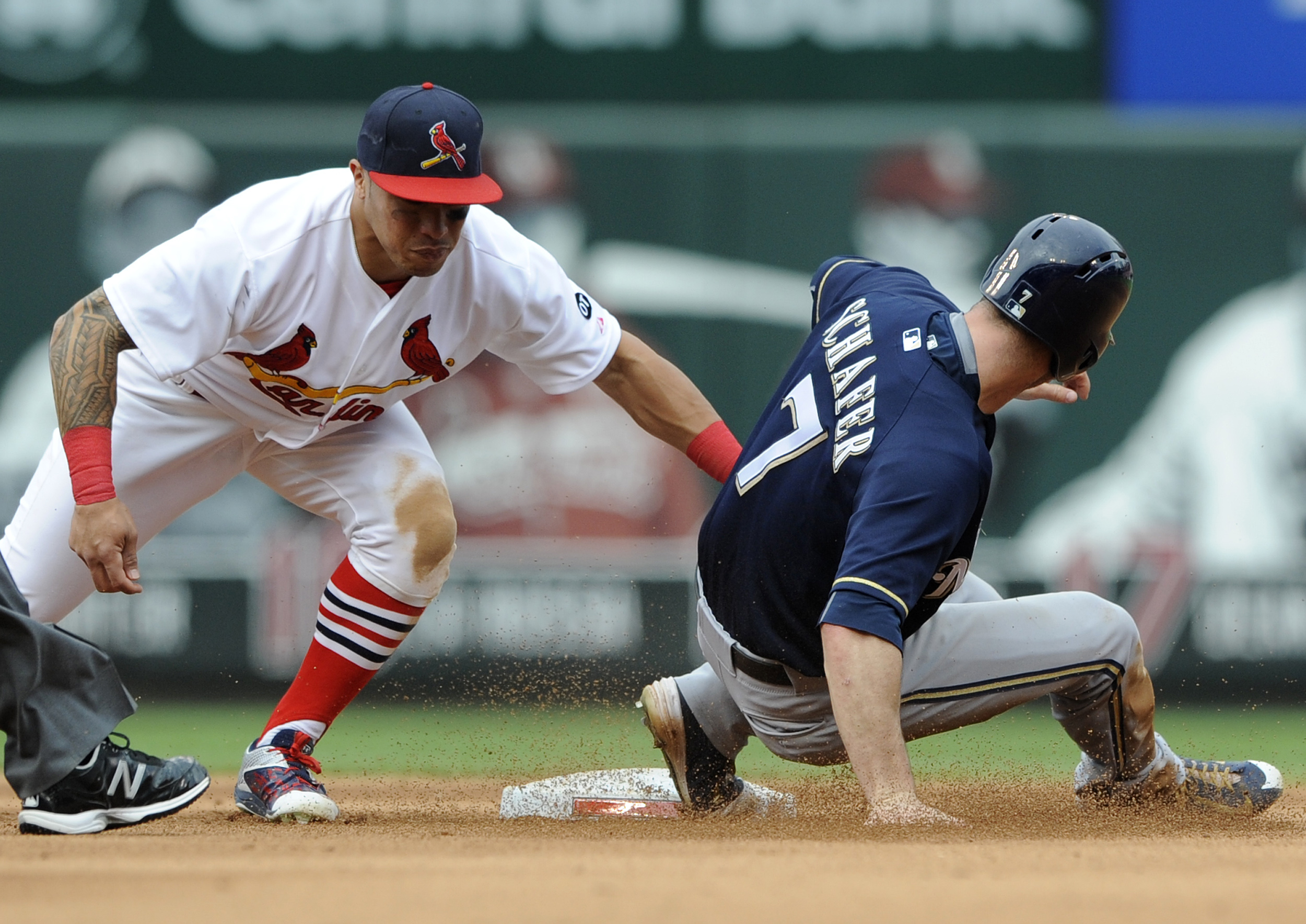 St. Louis Cardinals' Kolten Wong, left, cannot make the tag on Milwaukee Brewers' Logan Schaefer (7) in the sixth inning of a baseball game, Sunday, Sep. 27, 2015, at Busch Stadium in St. Louis. (AP Photo/Bill Boyce)