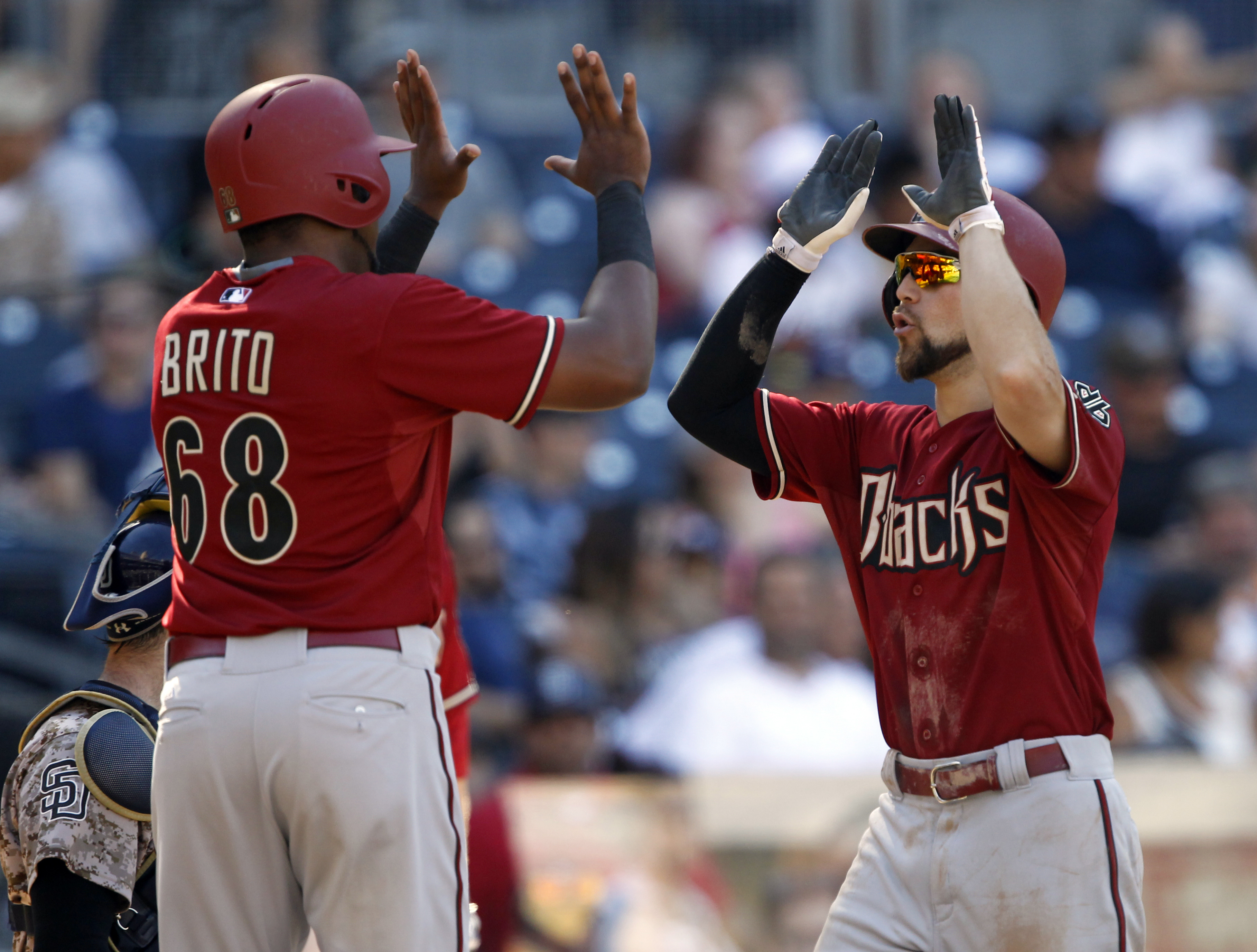 Arizona Diamondbacks' Socrates Brito, left, congratulates Ender Inciarte, right, for hitting a two-run home run against the San Diego Padres during the seventh inning of a baseball game in San Diego, Sunday, Sept. 27, 2015. (AP Photo/Alex Gallardo)