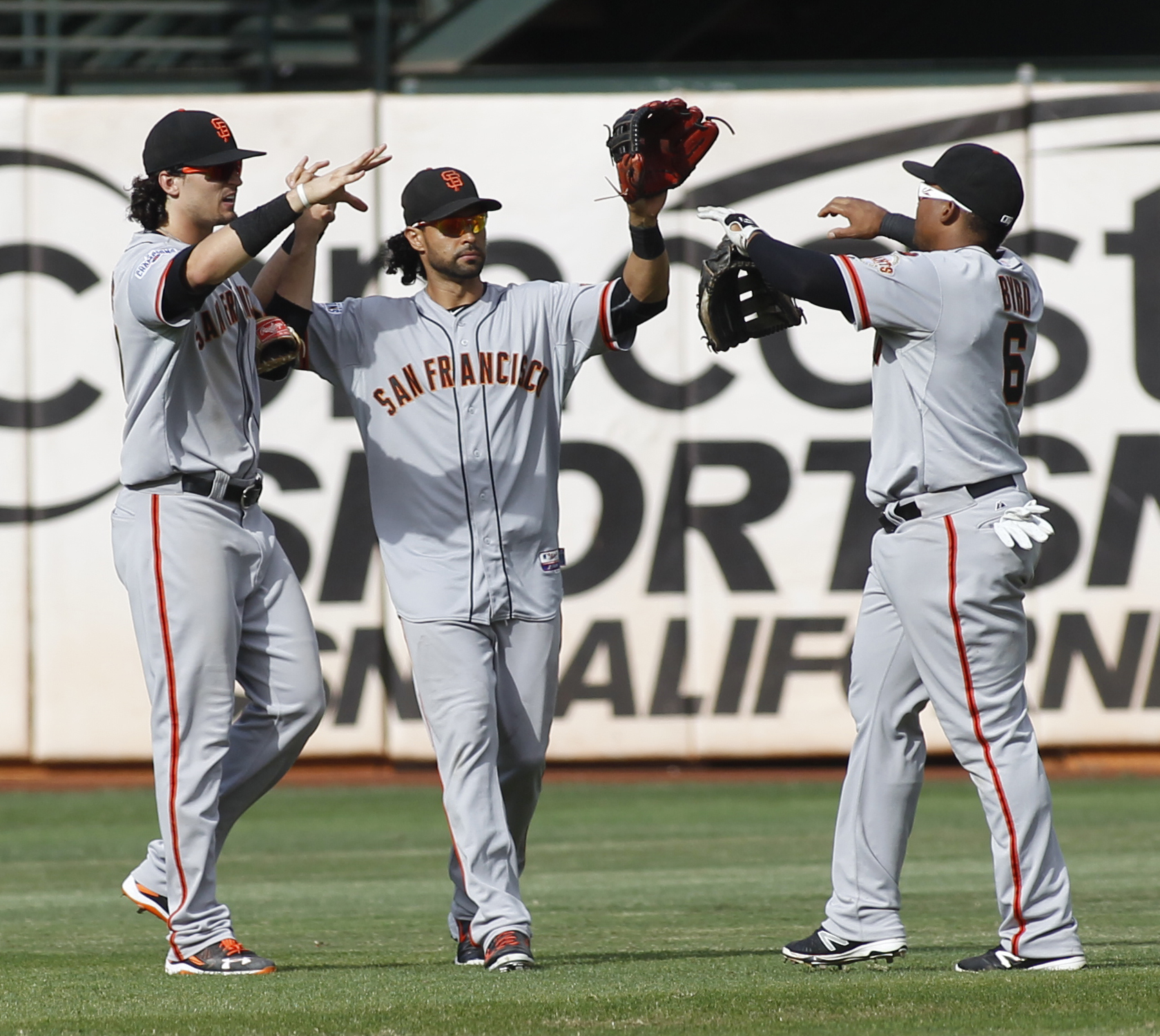San Francisco Giants' Jarrett Parker, left,  Angel Pagan, center, and Marlon Byrd celebrate after the Giants defeated the Oakland Athletics 5-4 in a baseball game, Sunday, Sept. 27, 2015, in Oakland, Calif. (AP Photo/George Nikitin)