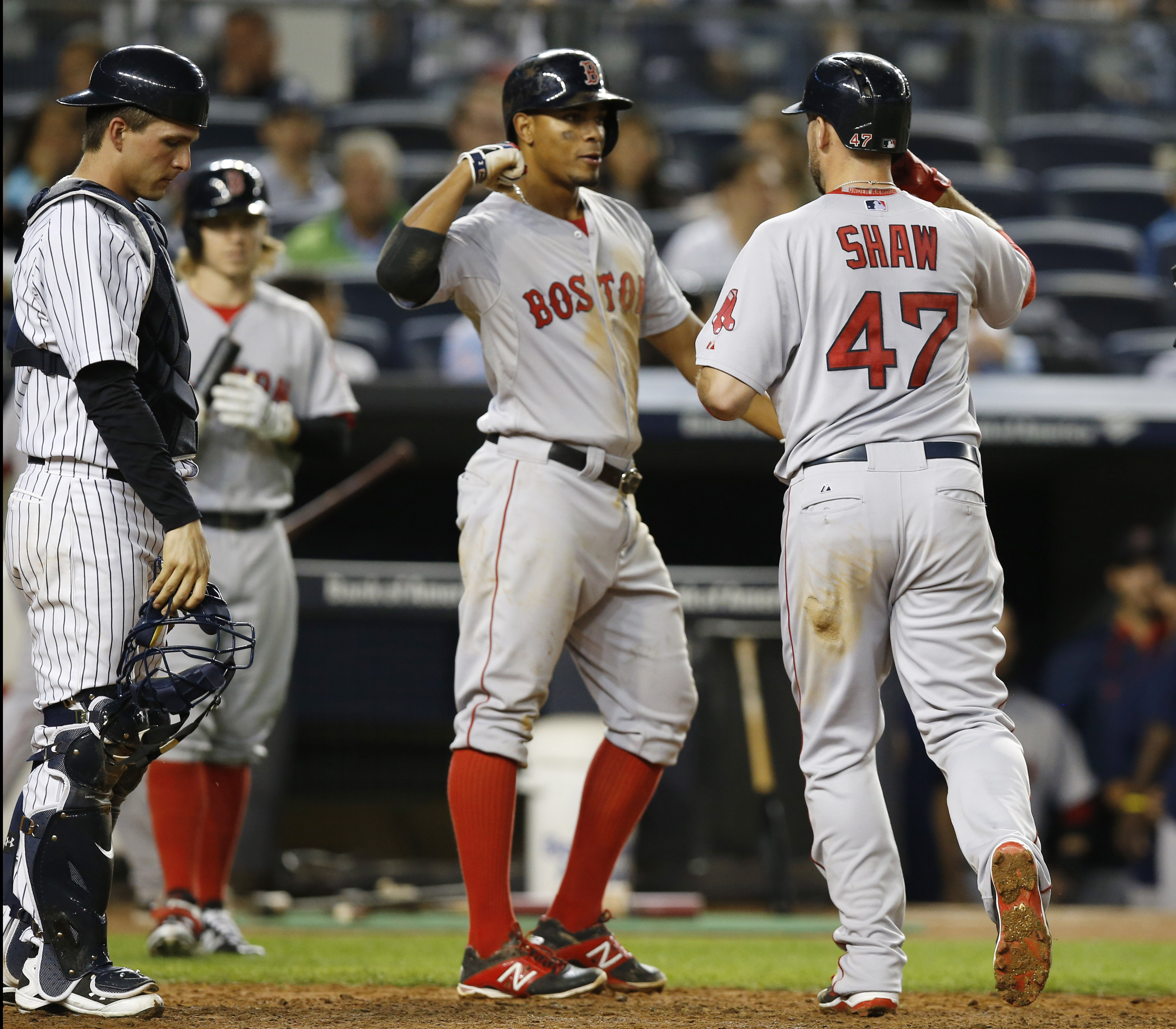 New York Yankees catcher John Ryan Murphy reacts as Boston Red Sox' Xander Bogaerts, center, greets Red Sox's Travis Shaw (47) after scoring on Shaw's sixth-inning, two-run, home run off New York Yankees starting pitcher Ivan Nova in a baseball game at Ya