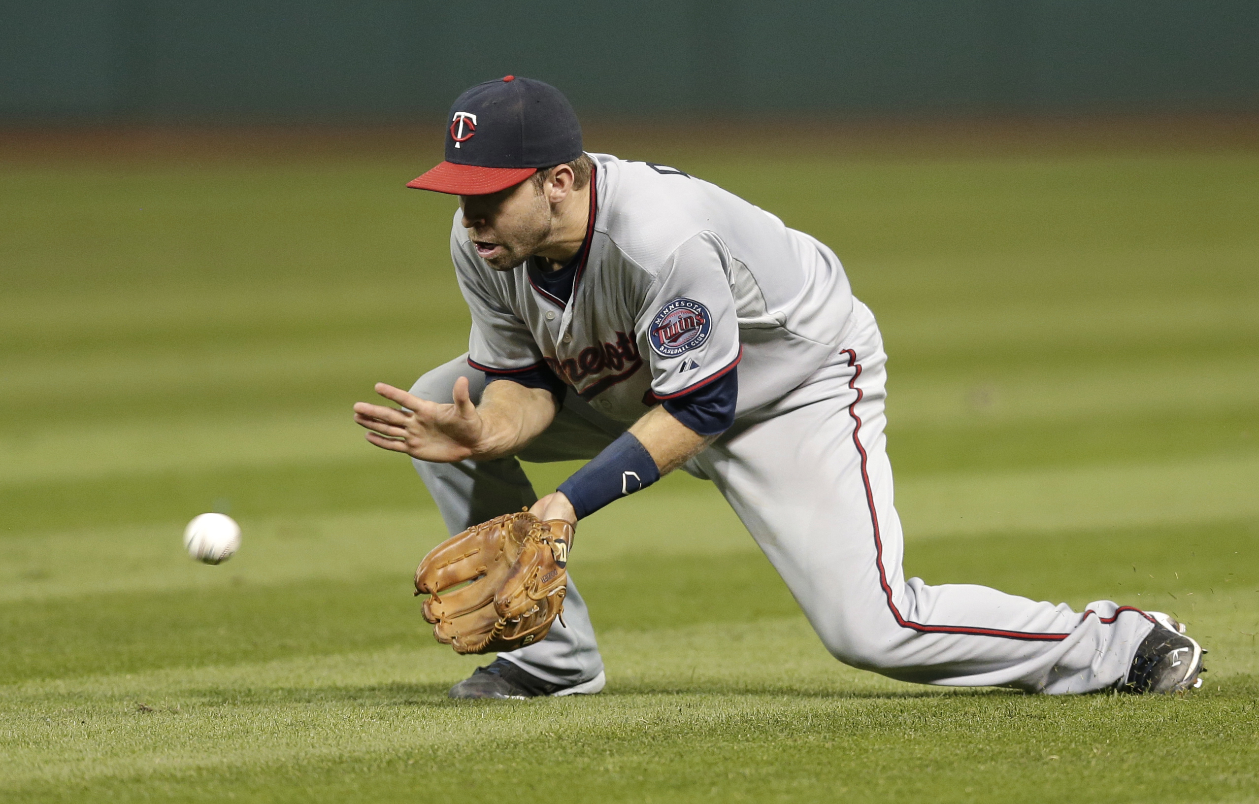 Minnesota Twins' Brian Dozier fields a ball hit by Cleveland Indians' Carlos Santana in the sixth inning of a baseball game, Monday, Sept. 28, 2015, in Cleveland. Santana was out on the play. (AP Photo/Tony Dejak)