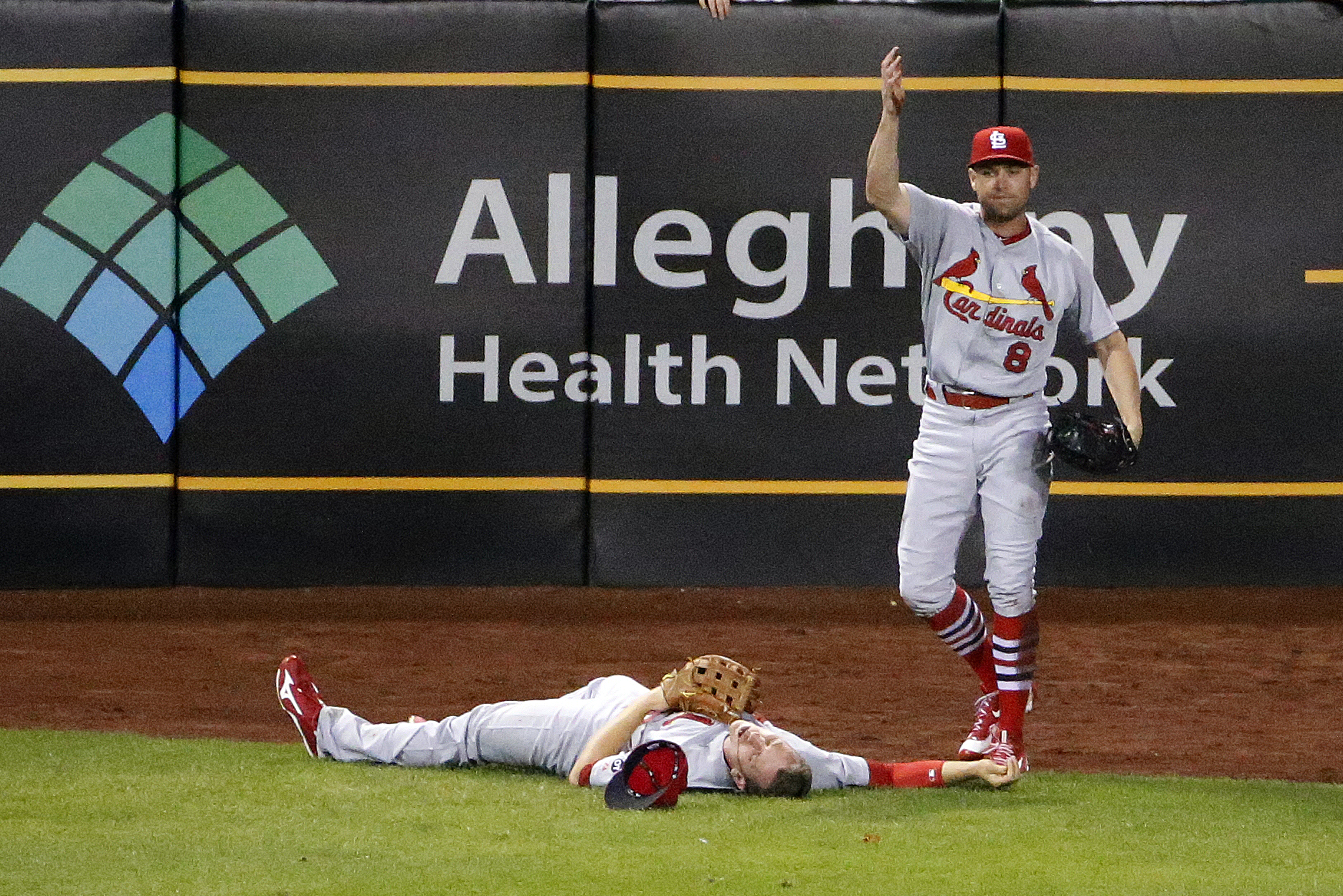 St. Louis Cardinals center fielder Peter Bourjos (8) calls for help after colliding with St. Louis Cardinals left fielder Stephen Piscotty while catching a fly ball by Pittsburgh Pirates' Josh Harrison in the seventh inning of a baseball game in Pittsburg