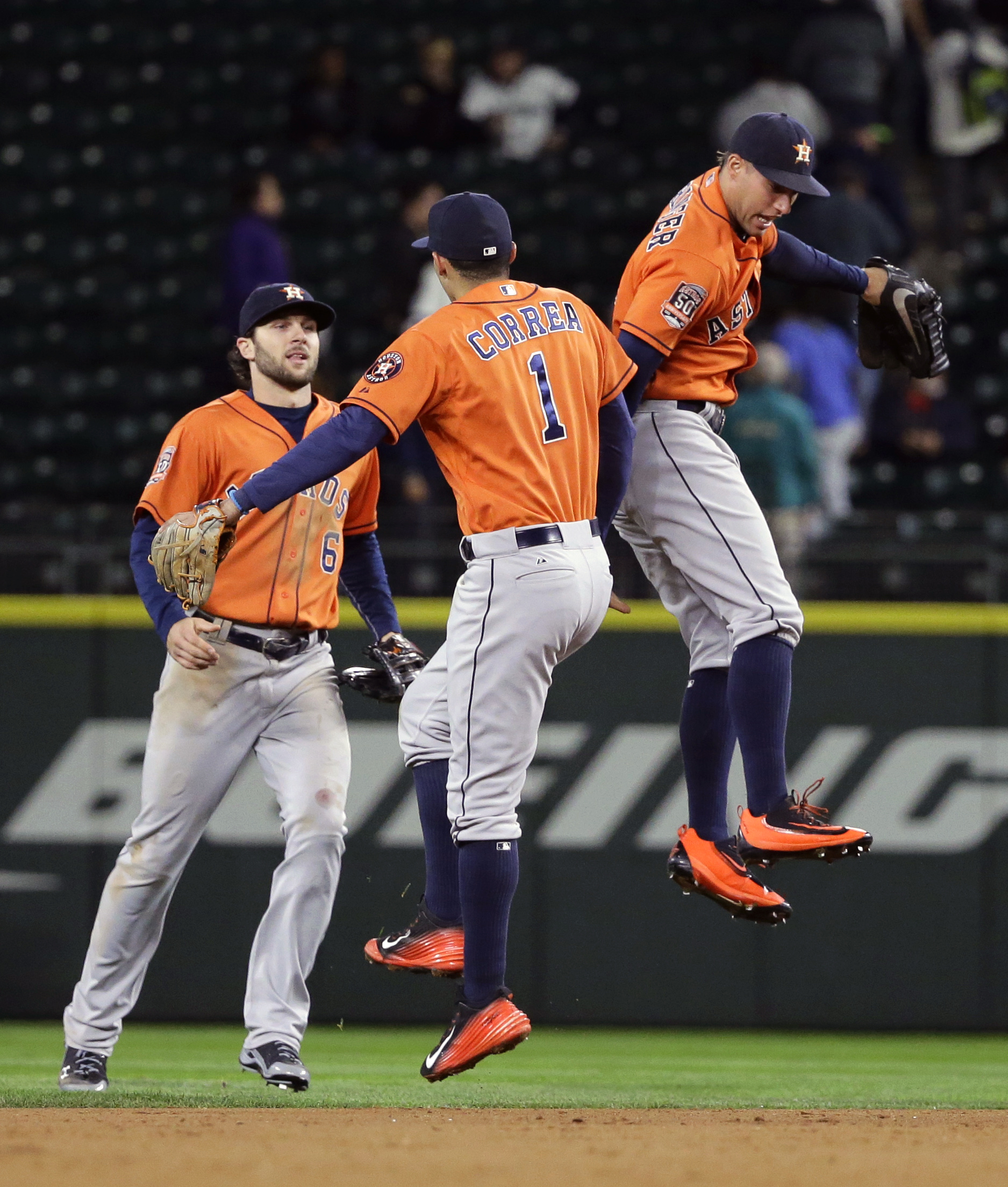 Houston Astros outfielder Jake Marisnick, left, shortstop Carlos Correa, center, and outfielder George Springer, right, celebrate after the Astros defeated the Seattle Mariners 3-2 in a baseball game, Monday, Sept. 28, 2015, in Seattle. (AP Photo/Ted S. W