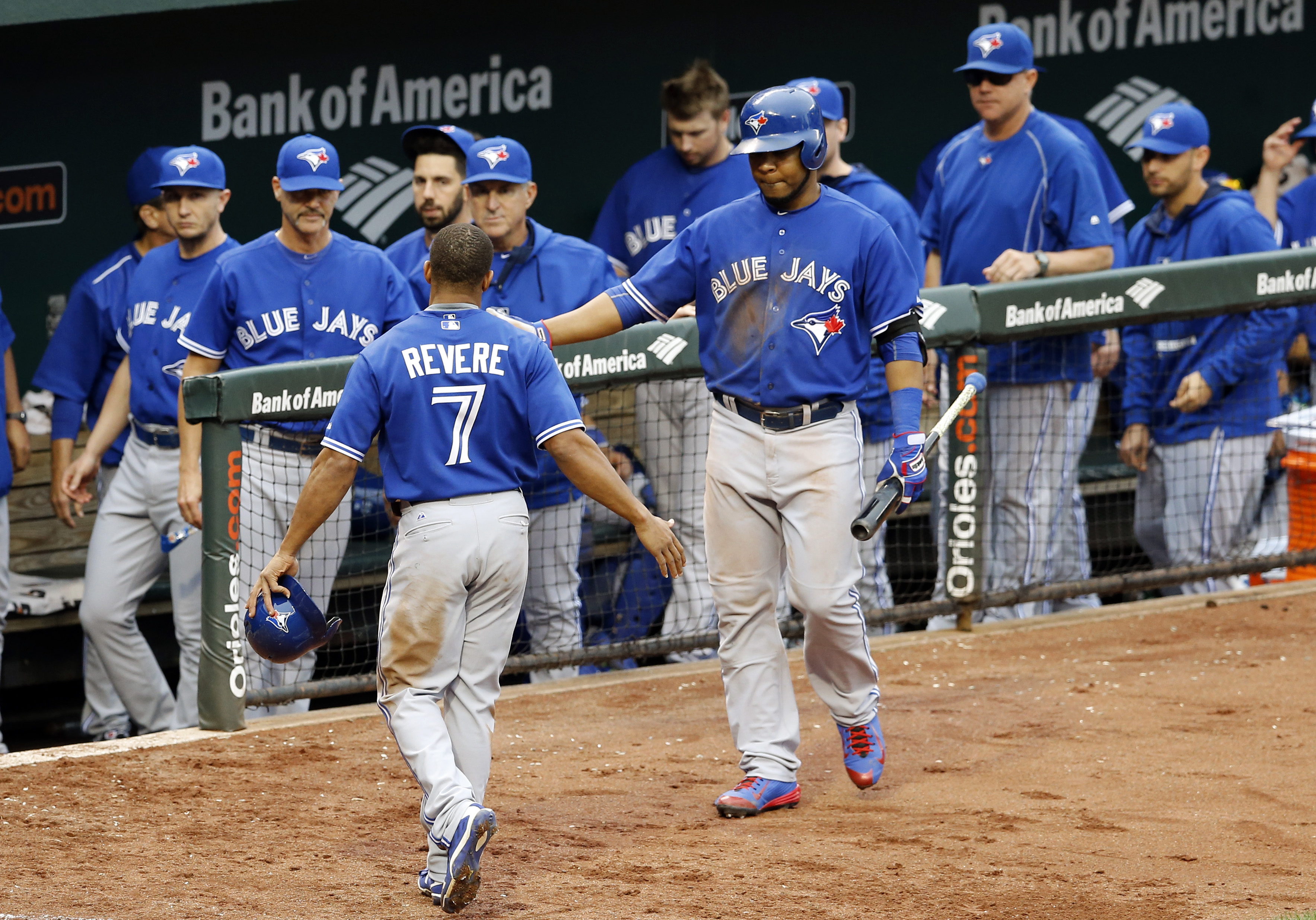 Toronto Blue Jays' Ben Revere (7) celebrates with teammate Edwin Encarnacion after scoring on a double by Josh Donaldson in the fifth inning in the first baseball game of a doubleheader against the Baltimore Orioles, Wednesday, Sept. 30, 2015, in Baltimor
