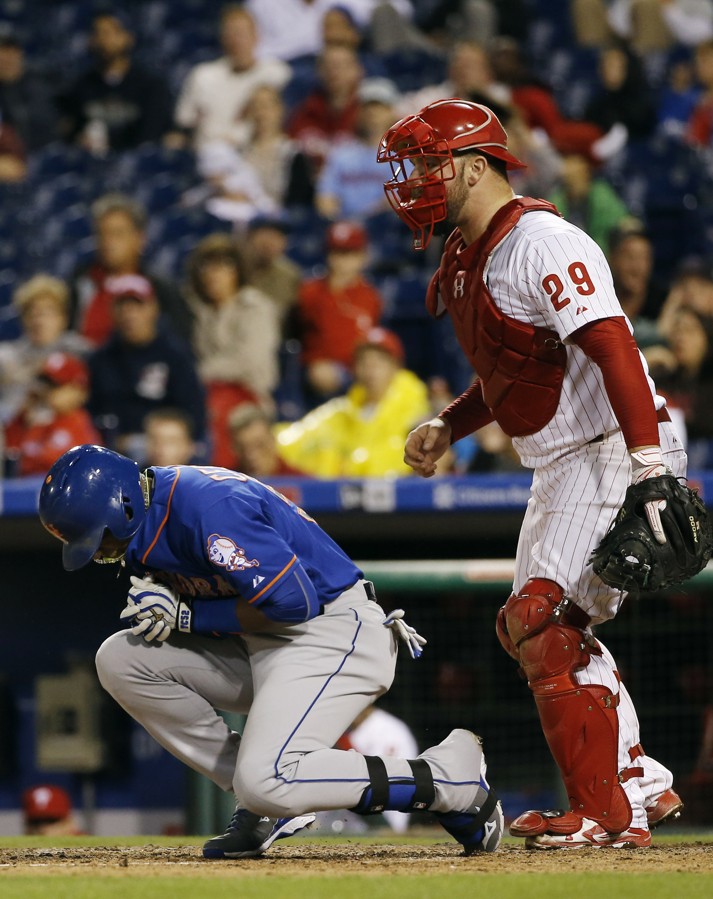 New York Mets' Yoenis Cespedes, left, reacts after being hit by a pitch from Philadelphia Phillies' Justin De Fratus as catcher Cameron Rupp looks on during the third inning of a baseball game, Wednesday, Sept. 30, 2015, in Philadelphia. (AP Photo/Matt Sl