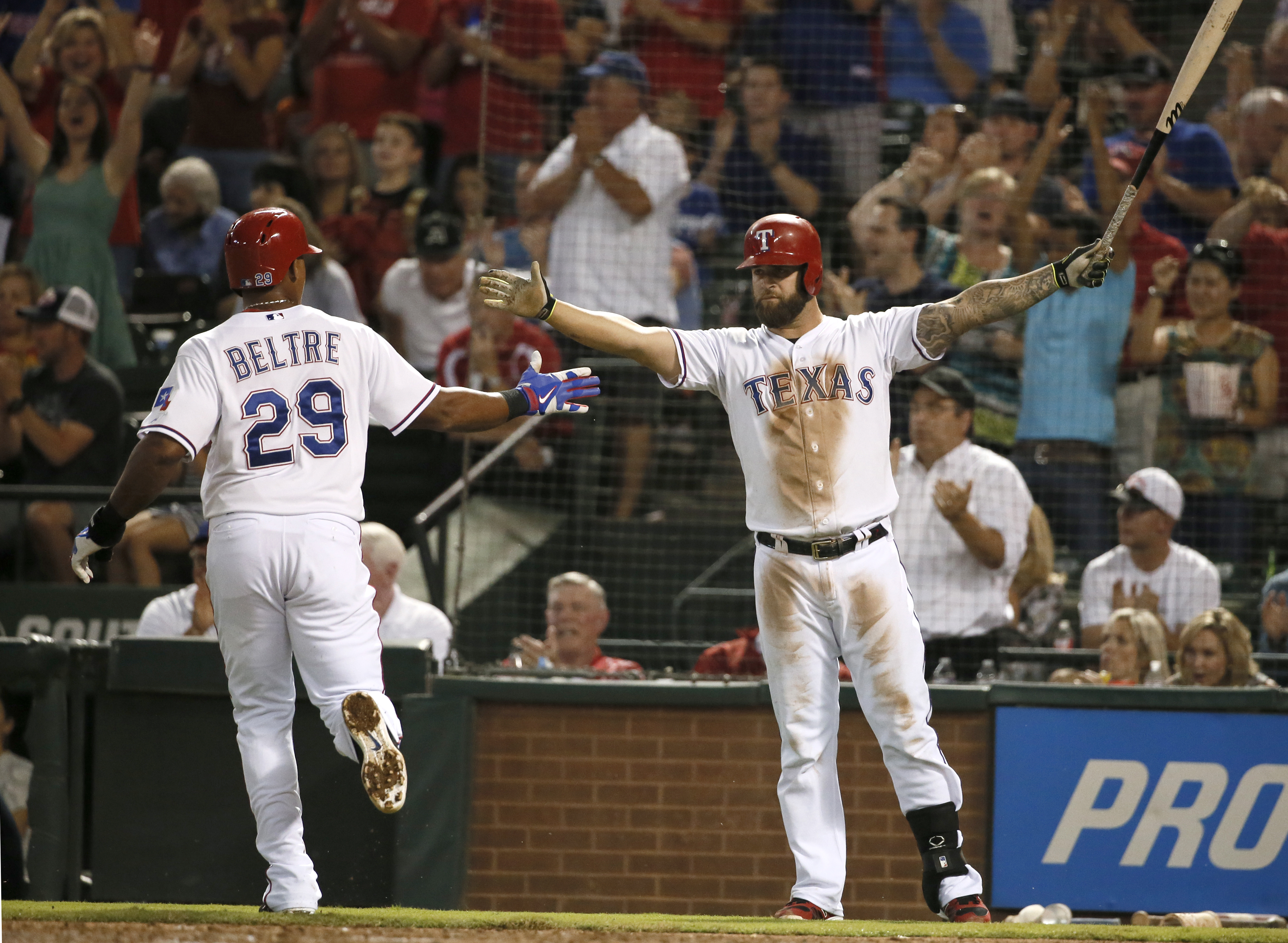 Texas Rangers' Adrian Beltre is congratulated on scoring by Mike Napoli, right, in the third inning of a baseball game against the Detroit Tigers, Wednesday, Sept. 30, 2015, in Arlington, Texas. (AP Photo/Tony Gutierrez)
