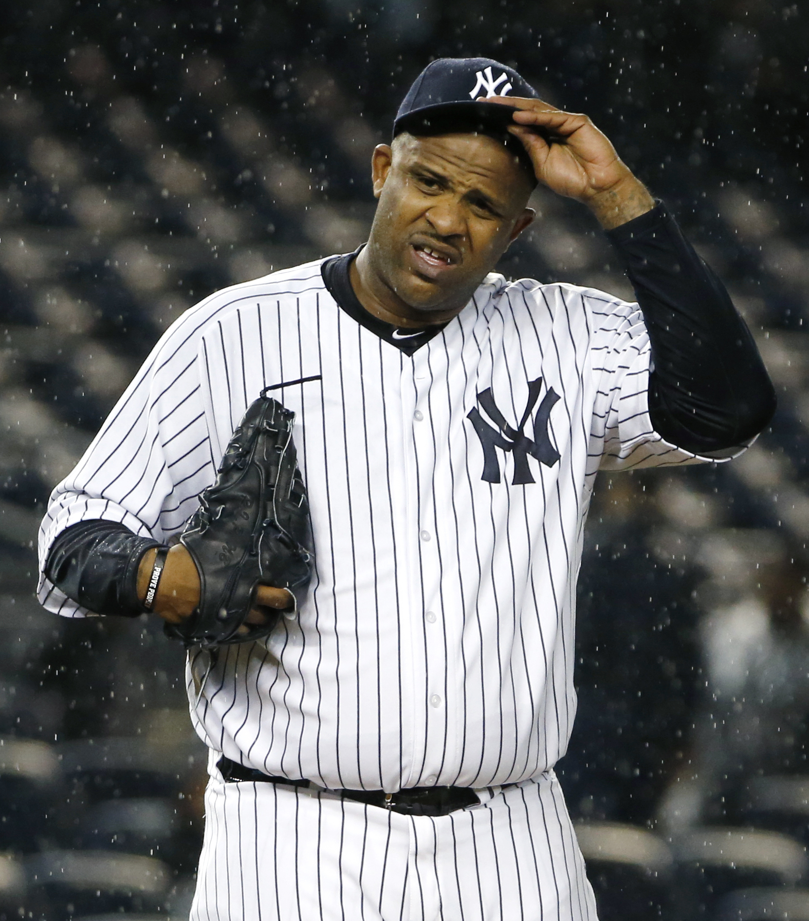 New York Yankees starting pitcher CC Sabathia (52) struggles with his cap in the rain during the first inning of a baseball game against the Boston Red Sox in New York, Thursday, Oct. 1, 2015.   (AP Photo/Kathy Willens)
