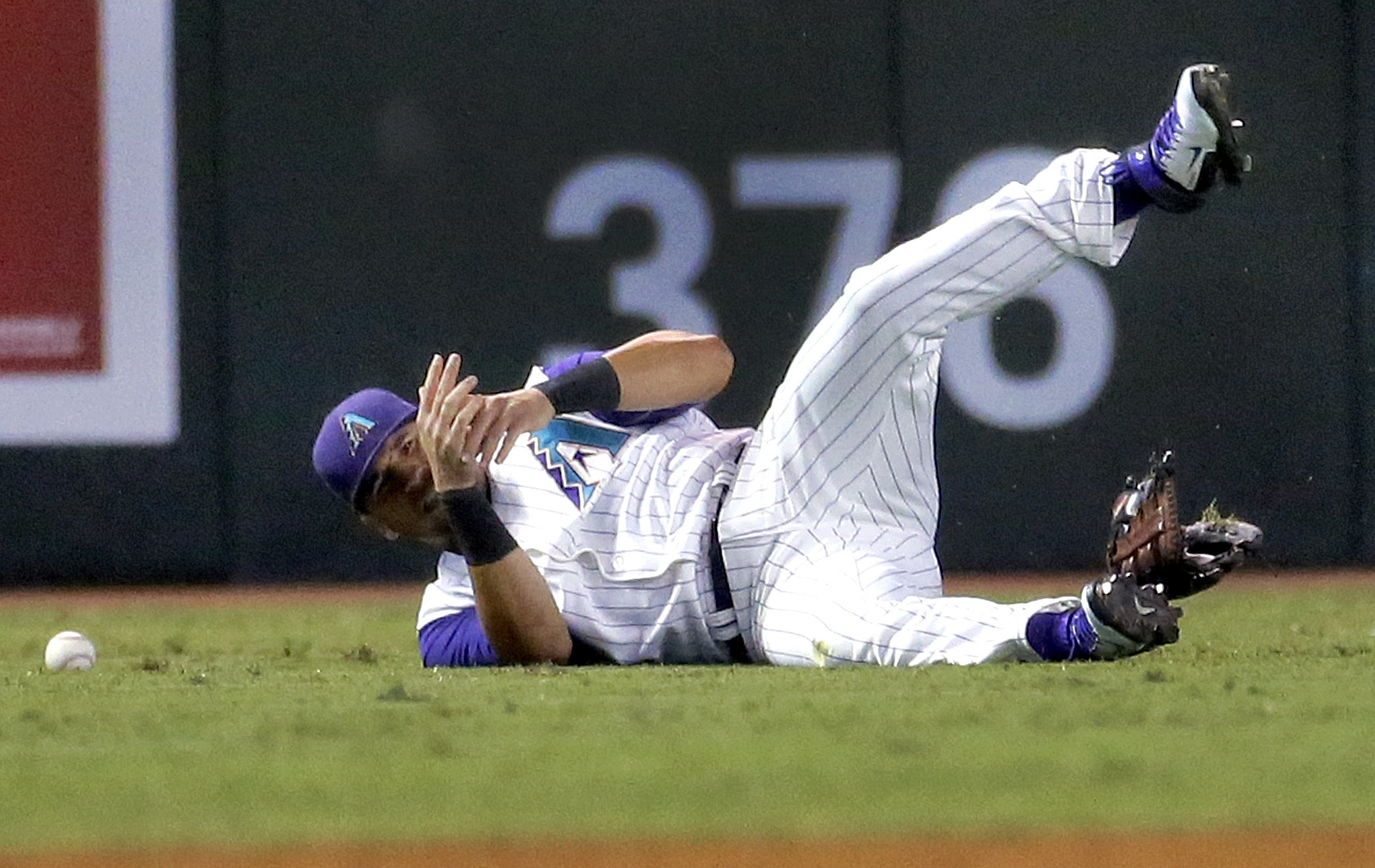 Arizona Diamondbacks' David Peralta grabs his wrist after being injured trying to catch a base hit by Colorado Rockies' Rafael Ynoa during the fourth inning of a baseball game, Thursday, Oct. 1, 2015, in Phoenix. Peralta left the game at the end of the in