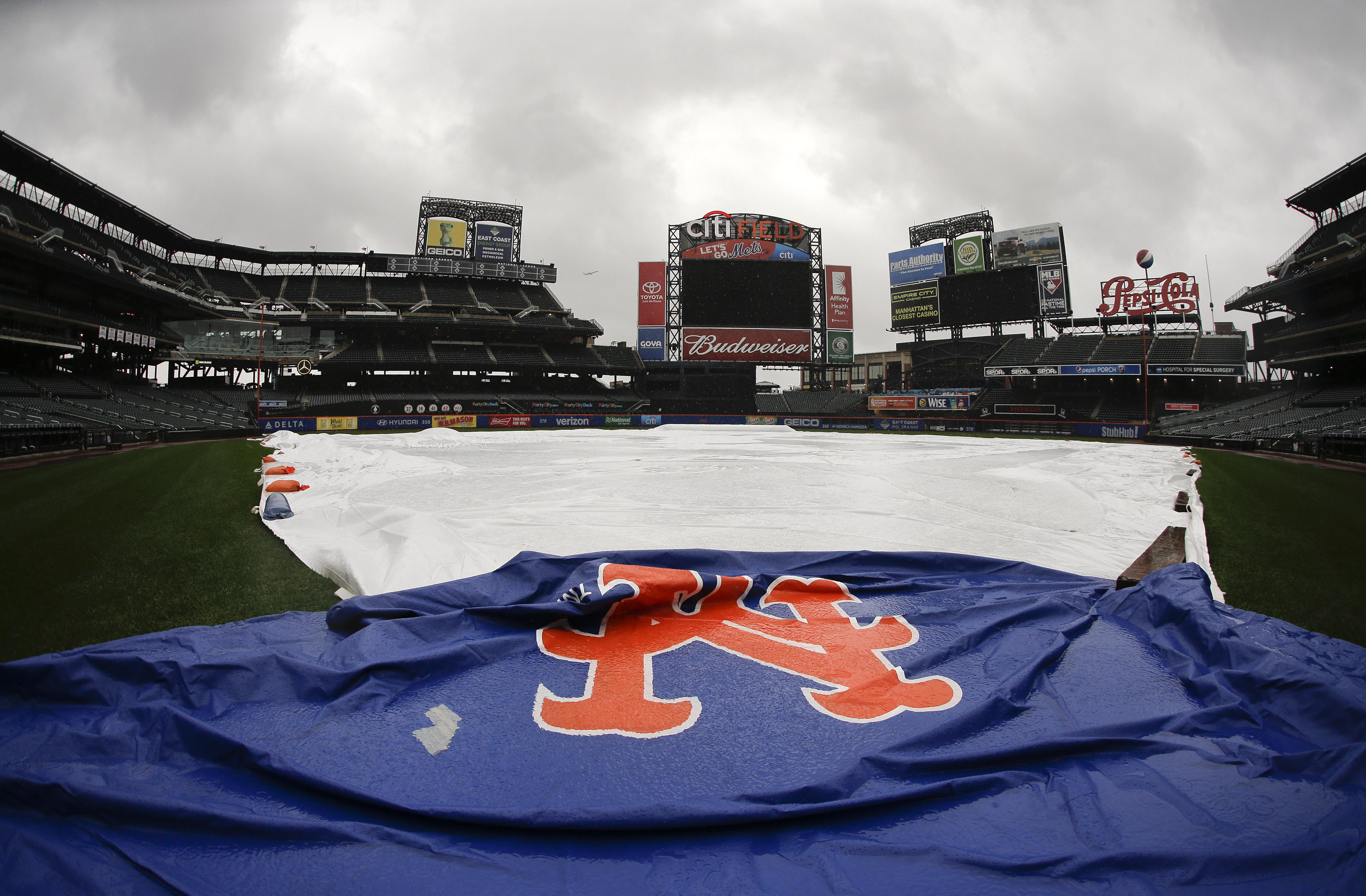 A tarp covers the field at Citi Field as a steady rain falls, Friday, Oct. 2, 2015, in New York. The baseball game between the Washington Nationals and New York Mets was postponed until Saturday because of rain. (AP Photo/Julie Jacobson)