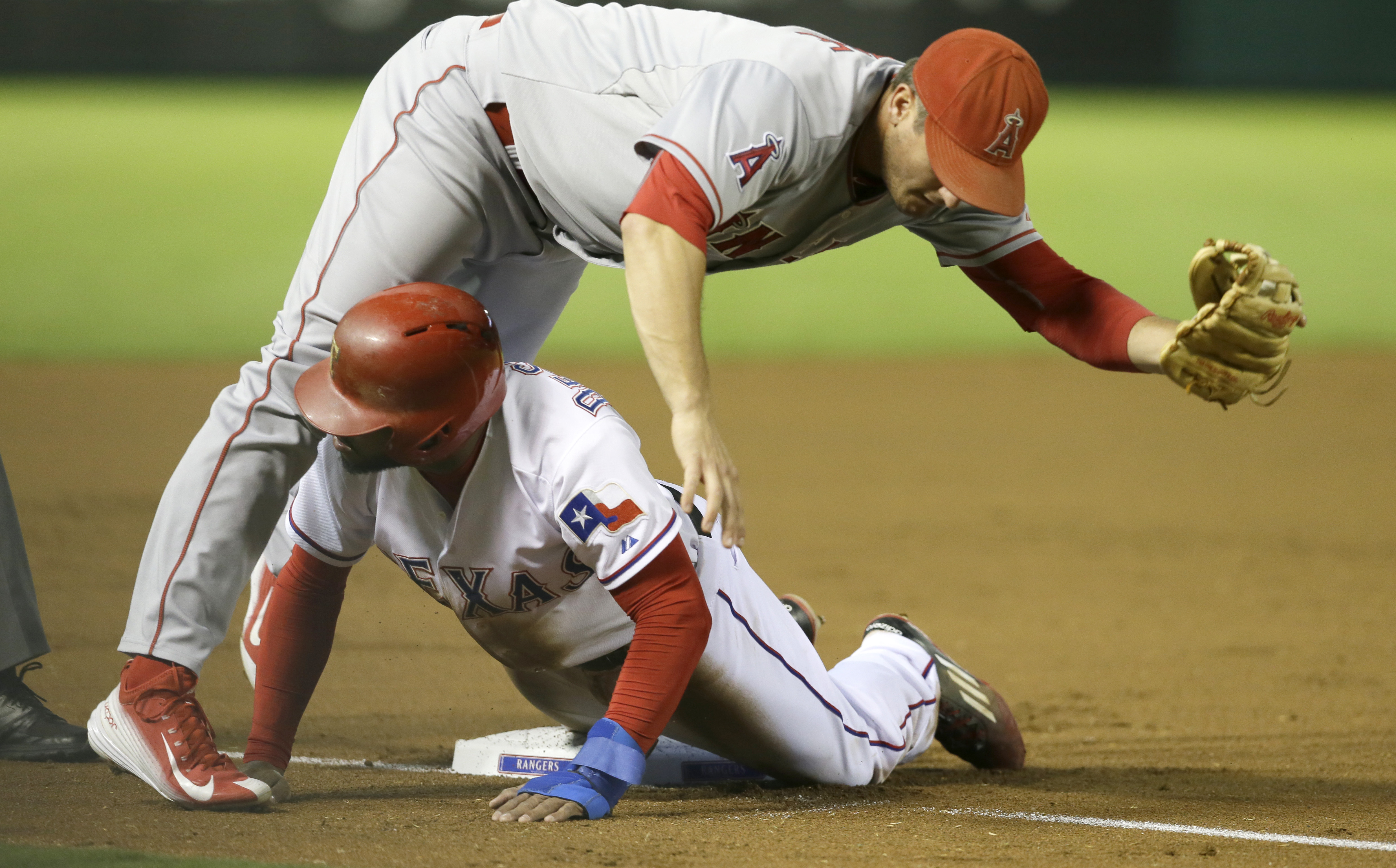 Texas Rangers Delino DeShields, bottom slides under third base against Los Angeles Angels third baseman David Freese (6) after DeShields was tagged out trying to steal during the first inning of a baseball game in Arlington, Texas, Friday, Oct. 2, 2015. (
