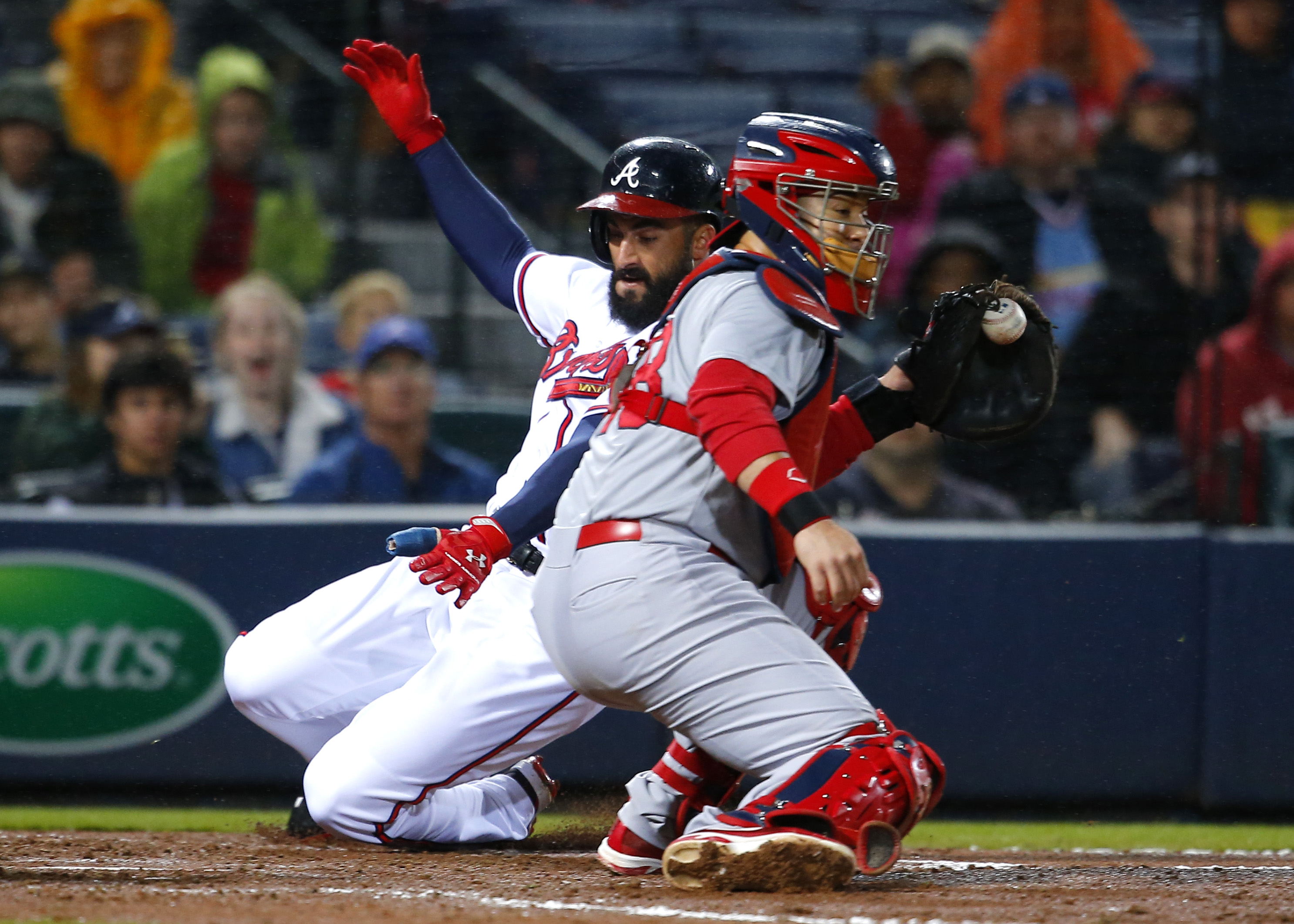 Atlanta Braves Nick Markakis slides in under the tag of St. Louis Cardinals catcher Tony Cruz (48) to score off the double of A.J. Pierzynski in the third inning of a baseball game against the St. Louis Cardinals, Friday, Oct. 2, 2015, in Atlanta. (AP Pho