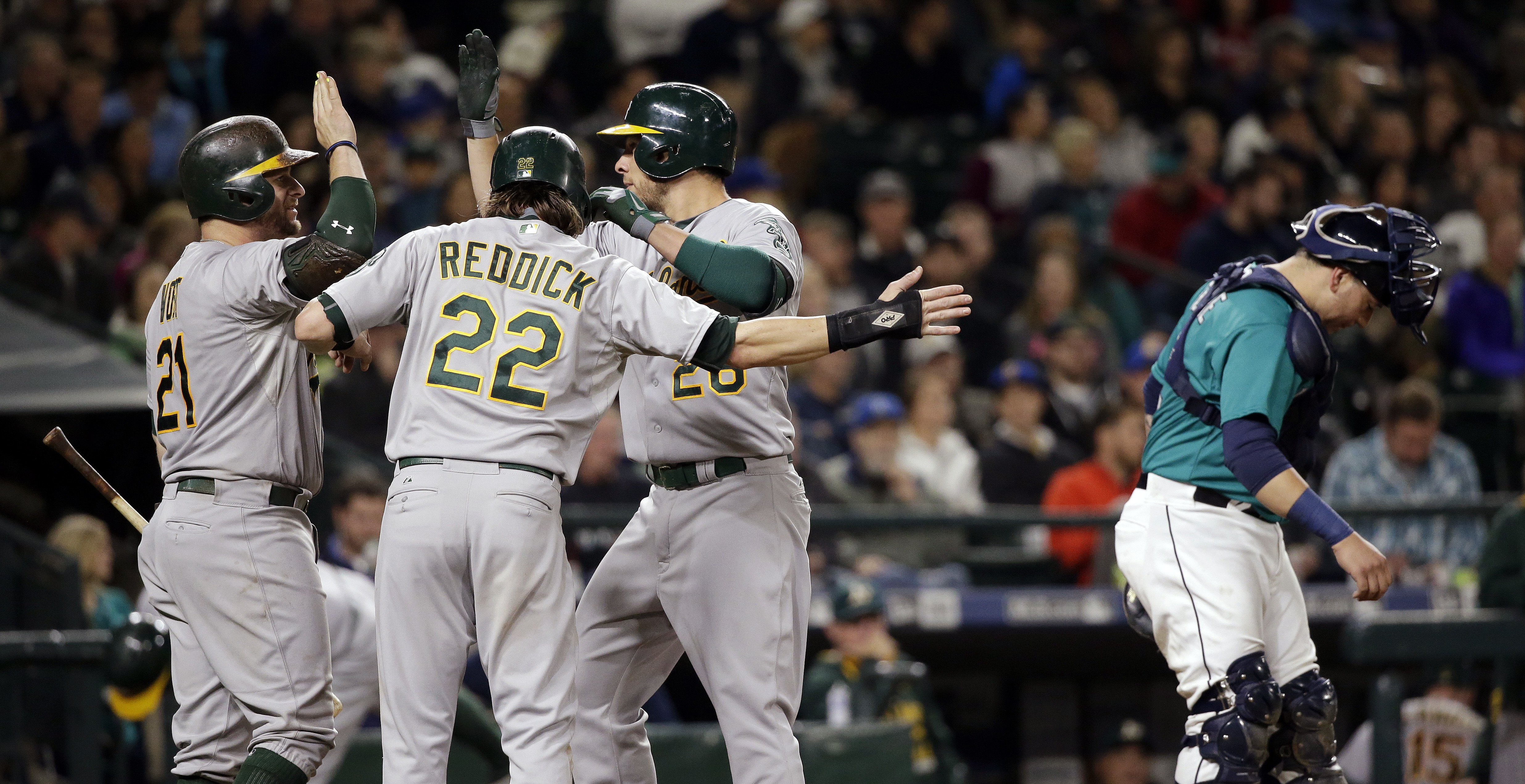 Oakland Athletics' Stephen Vogt (21) and Josh Reddick (22) greet Danny Valencia on his two-run home run as Seattle Mariners catcher Jesus Sucre waits for the next batter in the eighth inning of a baseball game Friday, Oct. 2, 2015, in Seattle. (AP Photo/E