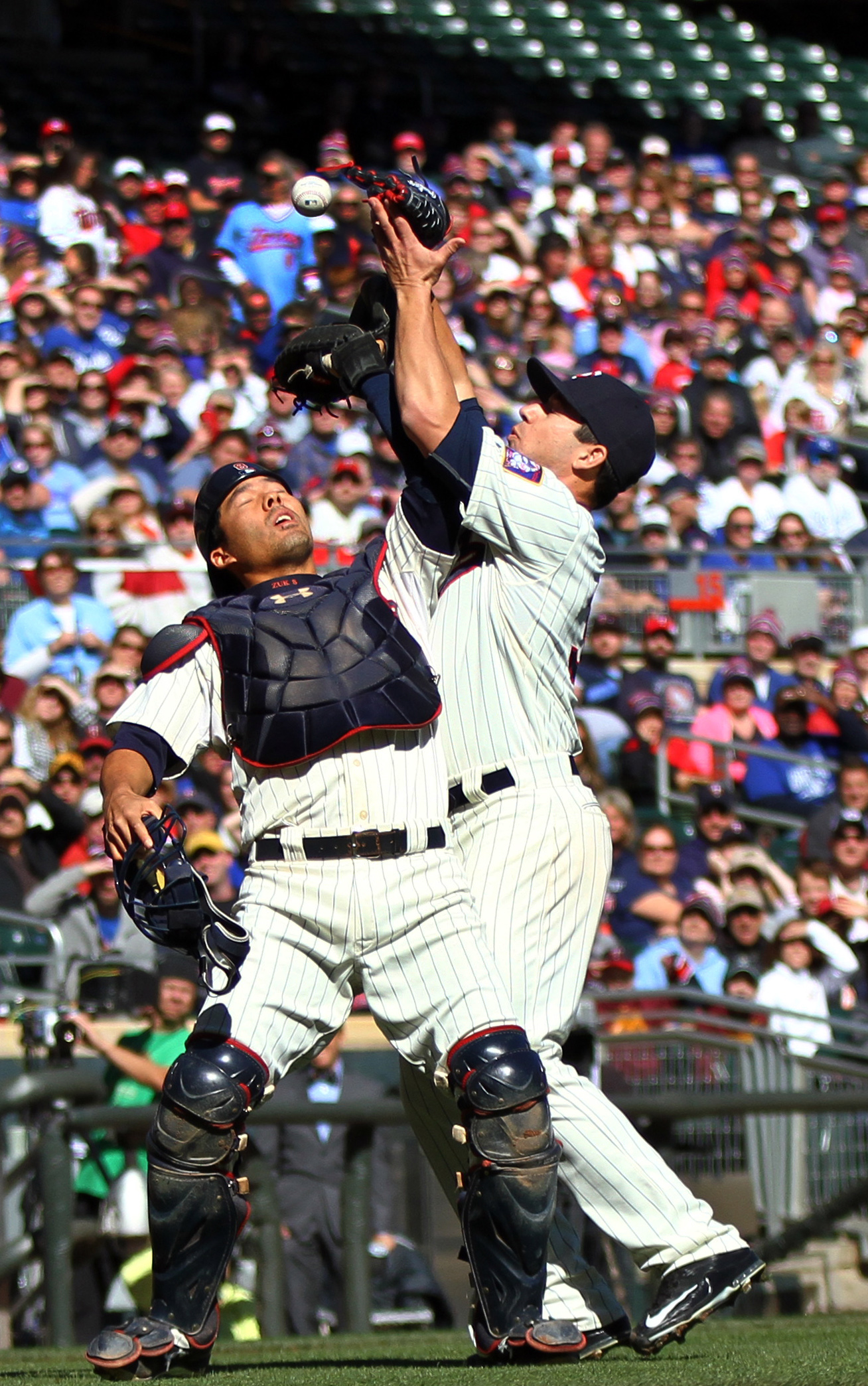 Minnesota Twins catcher Kurt Suzuki, left, and pitcher Tommy Milone collide while trying to catch a pop up hit by Kansas City Royals' Salvador Perez in the second inning of baseball game, Saturday, Oct. 3, 2015, in Minneapolis. Suzuki was given an error o