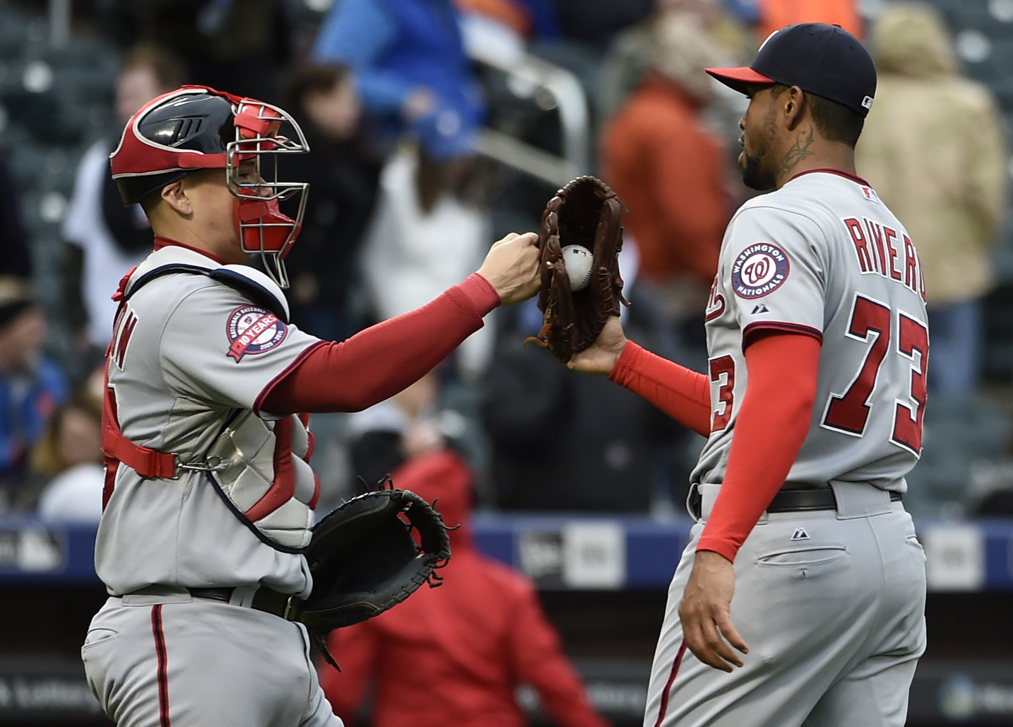 Washington Nationals catcher Jose Lobaton congratulates Washington Nationals relief pitcher Felipe Rivero (73) after the Nationals beat the New York Mets 3-1 in the first baseball game of a doubleheader, Saturday, Oct. 3, 2015, in New York. (AP Photo/Kath