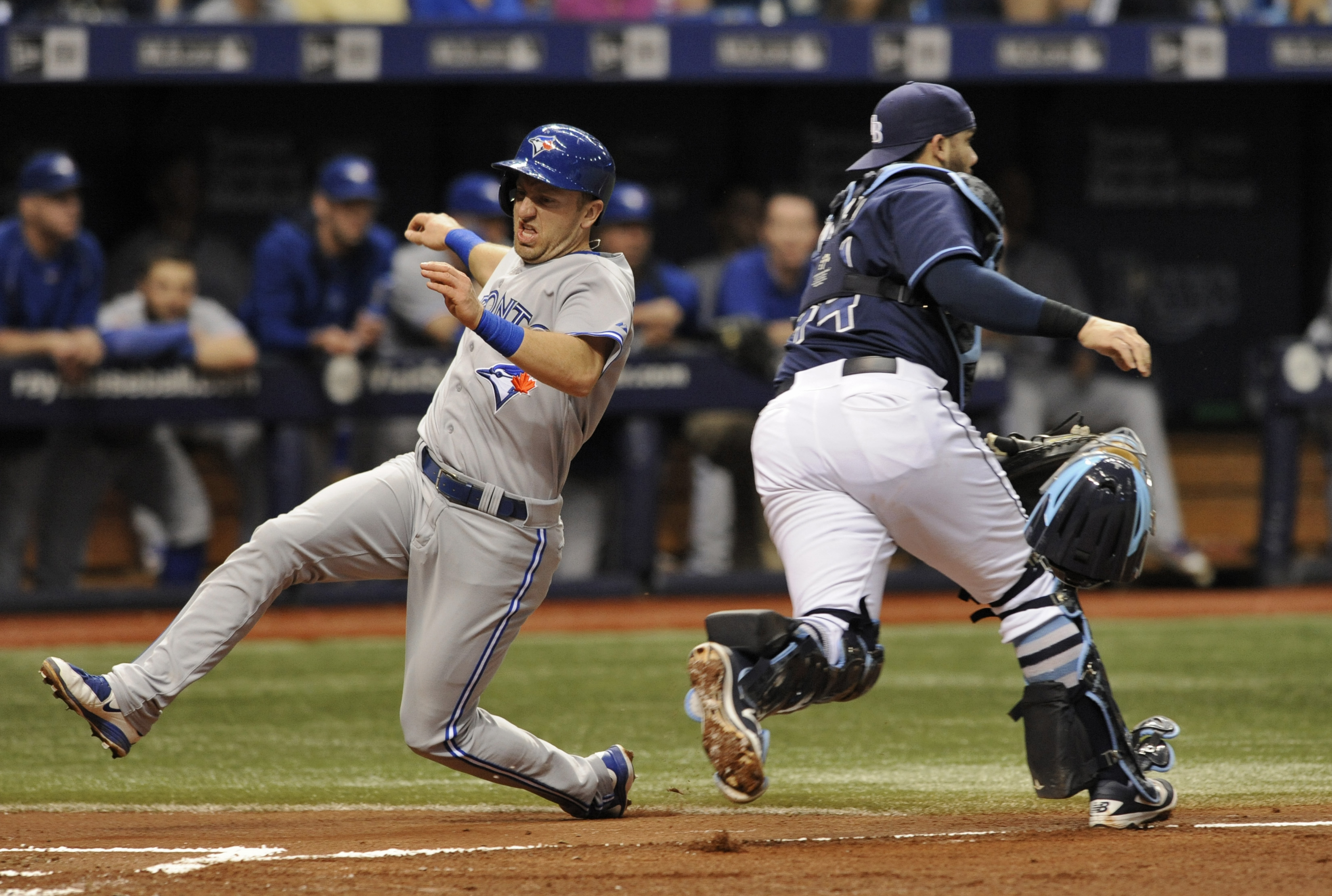 Toronto Blue Jays' Cliff Pennington, left, beats the throw to Tampa Bay Rays catcher Rene Rivera, right, to score on Toronto's Jose Bautista RBI-single during the third inning of a baseball game Saturday, Oct. 3, 2015, in St. Petersburg, Fla. (AP Photo/St