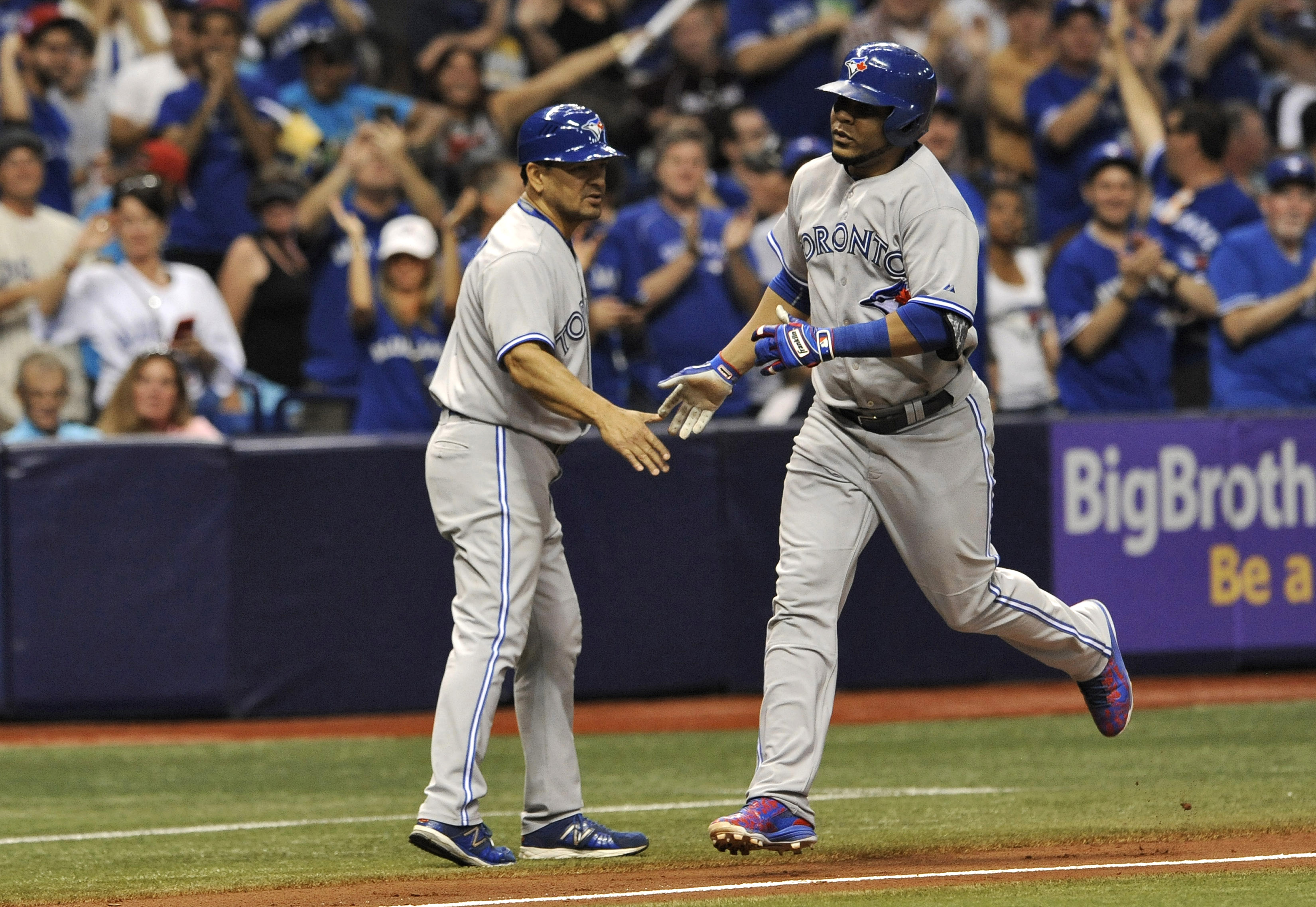 Toronto Blue Jays third base coach Luis Rivera, left, congratulates Edwin Encarnacion, right, as he circles the bases after hitting a two-run home run off Tampa Bay Rays reliever Brandon Gomes during the sixth inning of a baseball game Saturday, Oct. 3, 2