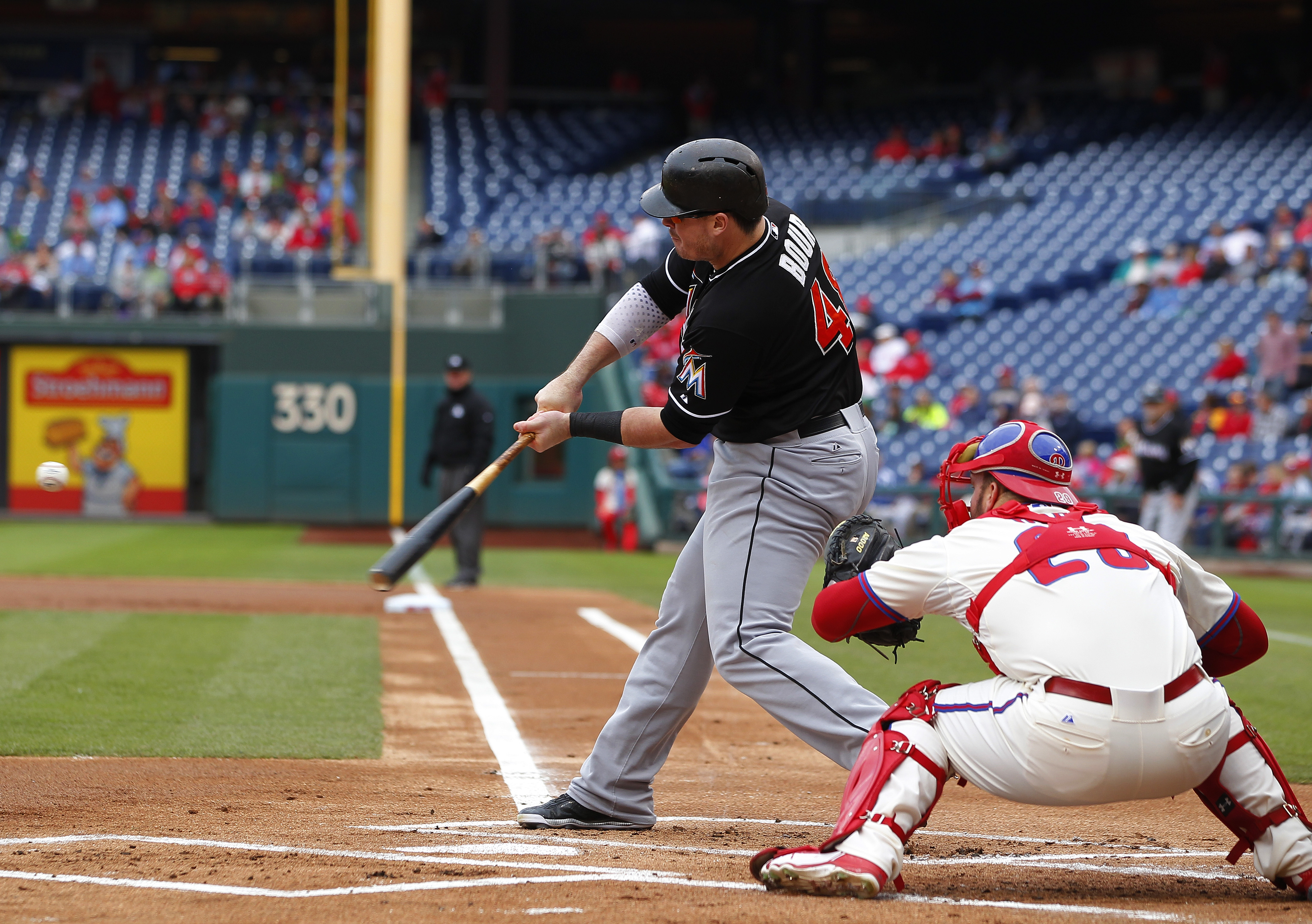Miami Marlins'Justin Bour, left, hits an RBI-single against the Philadelphia Phillies during the first inning of a baseball game Sunday, Oct. 4, 2015, in Philadelphia. (AP Photo/Rich Schultz)