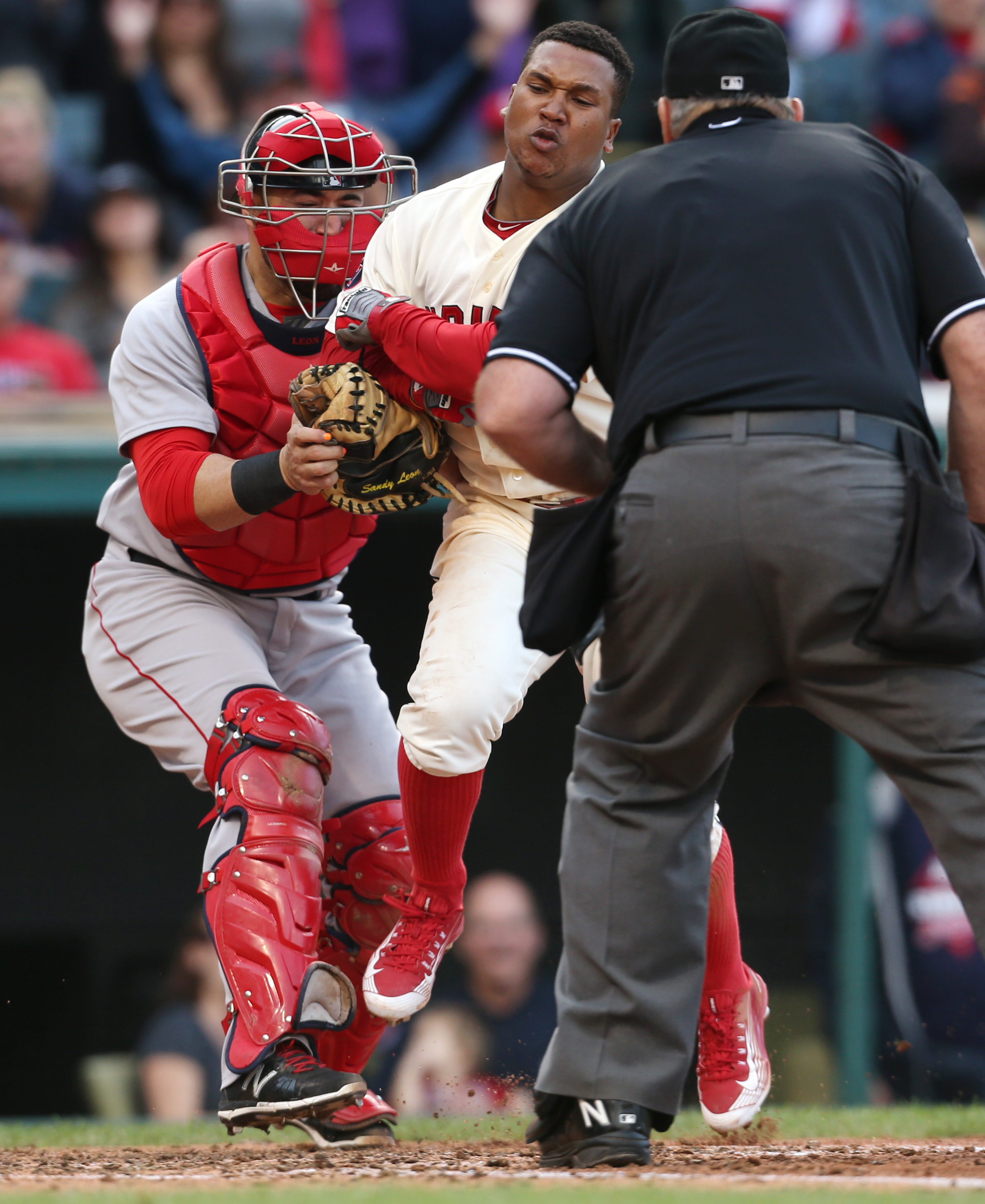 Cleveland Indians' Jose Ramirez is tagged out at home plate by Boston Red Sox' Sandy Leon as umpire Bob Davidson makes the call during the fifth inning of a baseball game, Sunday, Oct. 4, 2015, in Cleveland. (AP Photo/Ron Schwane)