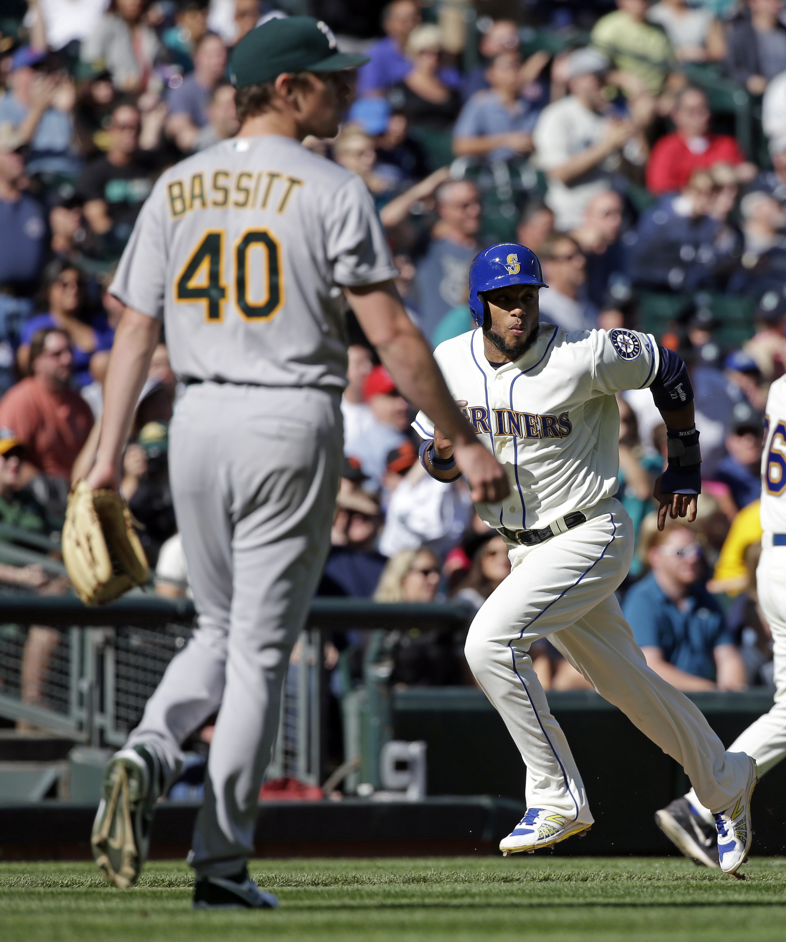 Seattle Mariners' Robinson Cano, right, heads home to score on a sacrifice fly by Logan Morrison as Oakland Athletics starting pitcher Chris Bassitt (40) looks on in the fourth inning of a baseball game Sunday, Oct. 4, 2015, in Seattle. (AP Photo/Elaine T
