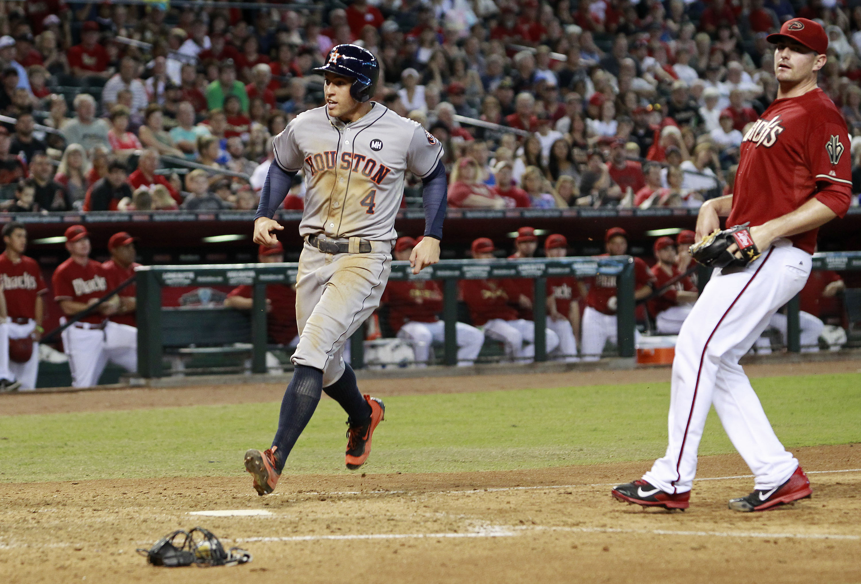 Houston Astros's George Springer (4) crosses the plate to score the game tying run on a wild pitch by Arizona Diamondbacks' Daniel Hudson,right, during the seventh inning of a baseball game, Sunday, Oct. 4, 2015, in Phoenix. (AP Photo/Ralph Freso)