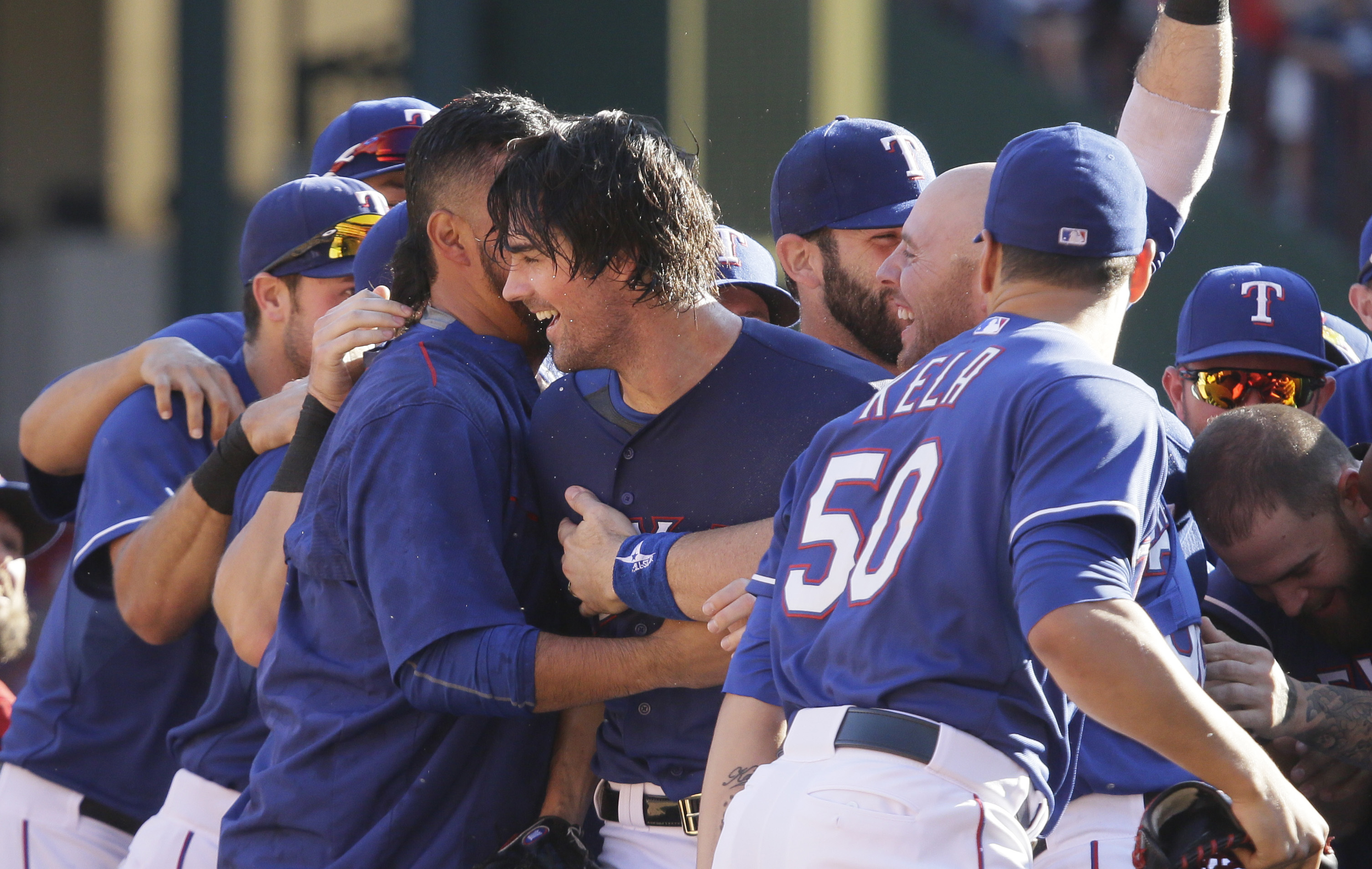 Texas Rangers starting pitcher Cole Hamels, center, is mobbed by his teammates after the final out of the baseball game against the Los Angeles Angels in Arlington, Texas, Sunday, Oct. 4, 2015. The Rangers clinched the AL West title on the last day of the
