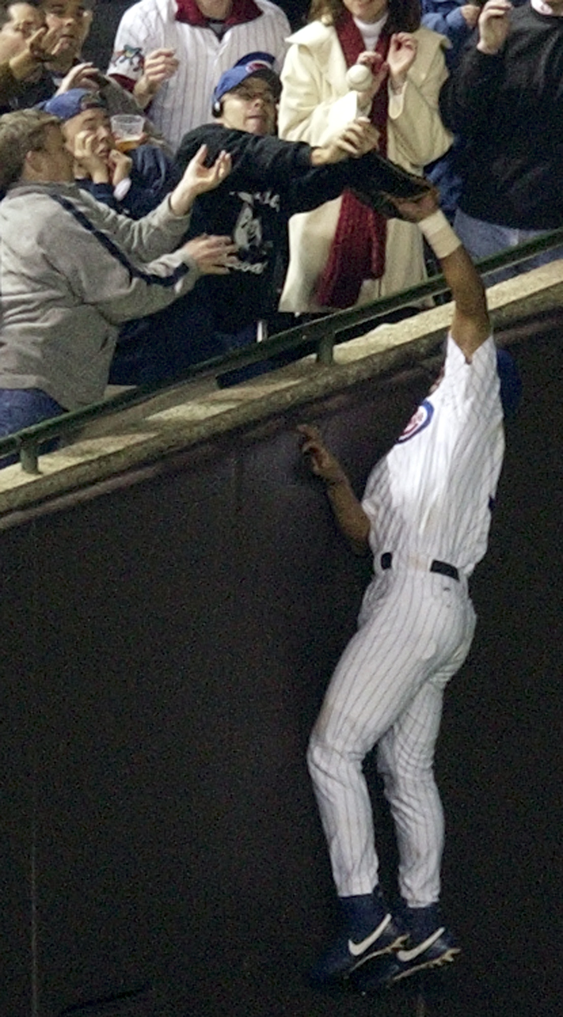 FILE - In this Oct. 14, 2003, file photo, Chicago Cubs left fielder Moises Alou reaches into the stands unsuccessfully for a foul ball, as Cubs fan Steve Bartman also reaches for the ball, during the eighth inning during Game 6 of the National League cham