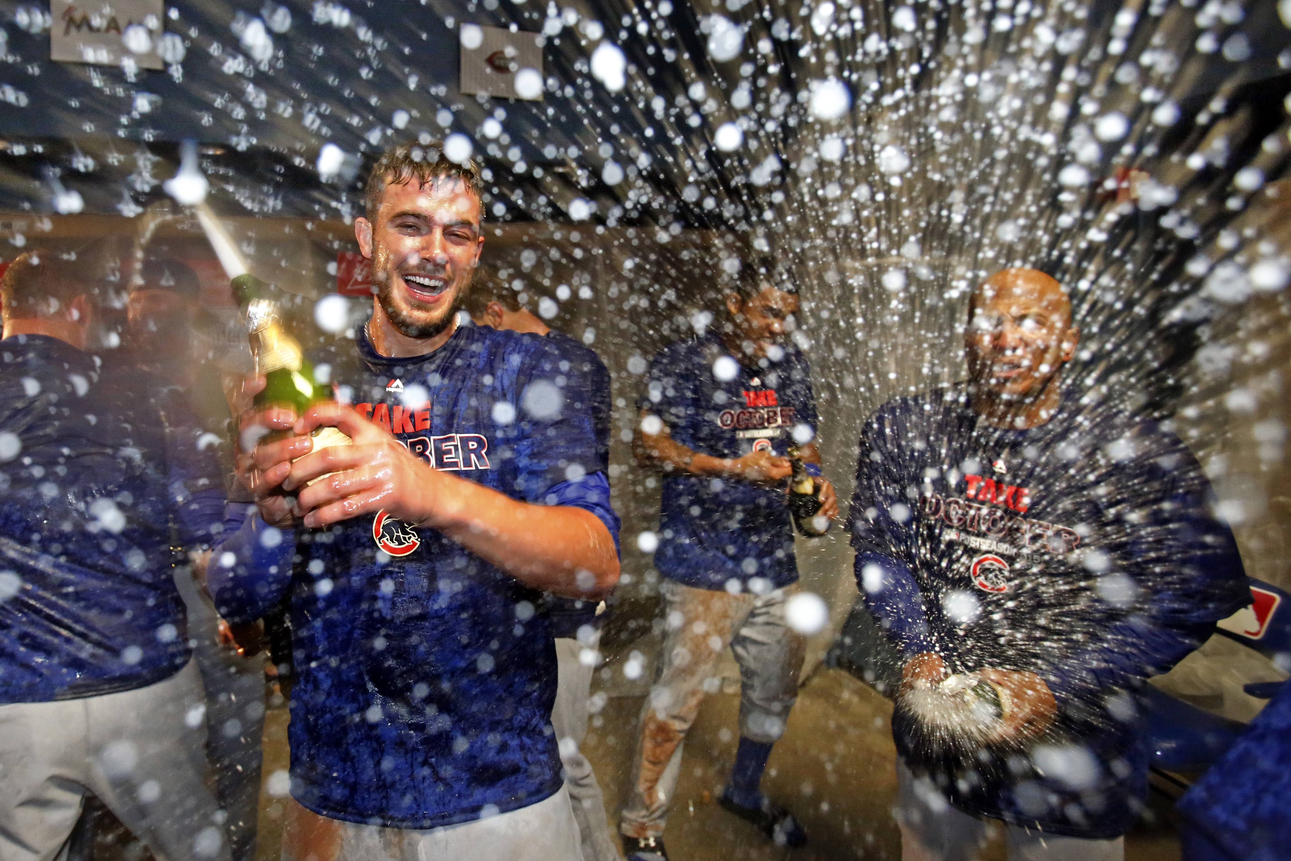 Chicago Cubs' Kris Bryant, left, celebrates with teammates in their locker room after a 4-0 win over the Pittsburgh Pirates in the National League wild card baseball game Wednesday, Oct. 7, 2015, in Pittsburgh. The Cubs advance to face the St. Louis Cardi