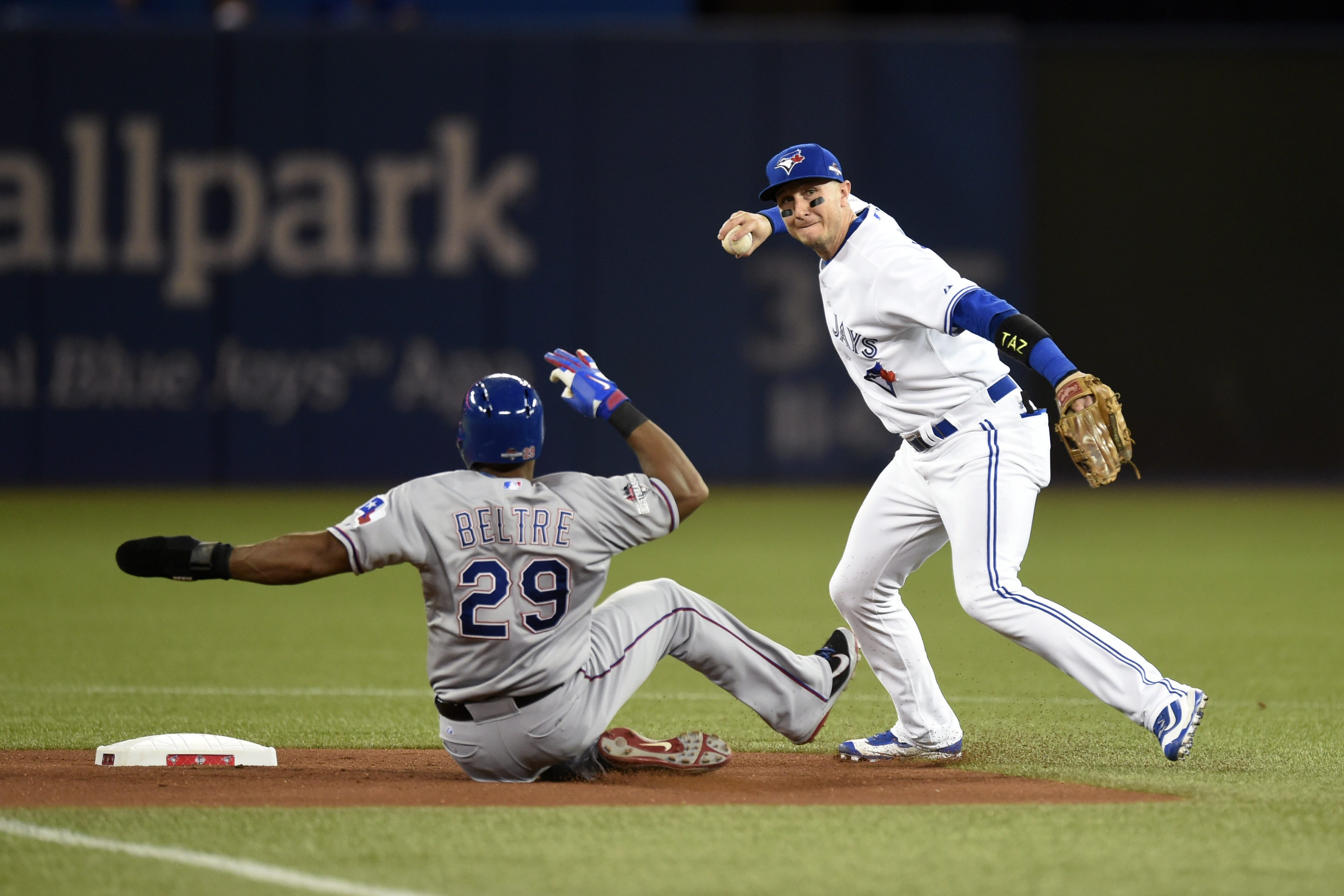Toronto Blue Jays' shortstop Troy Tulowitzki forces out Texas Rangers' Adrian Beltre at second base before throwing to first base for the double play during the first inning in Game 1 of an American League Division Series in Toronto on Thursday, Oct. 8, 2