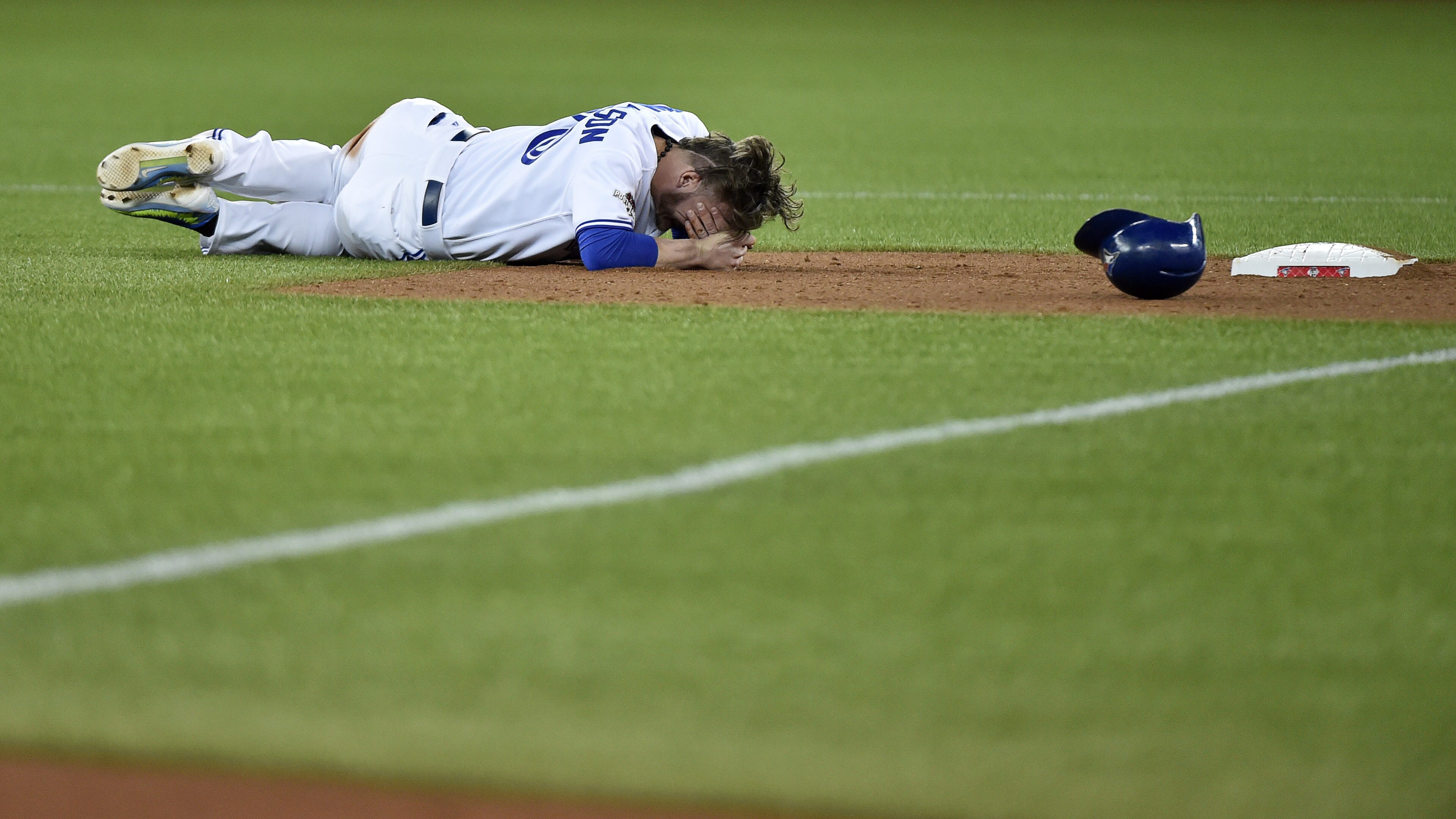 Toronto Blue Jays' Josh Donaldson lies on the ground after breaking up a double play during the fourth inning of Game 1 of the American League Division Series in Toronto on Thursday, Oct. 8, 2015. (Nathan Denette/The Canadian Press via AP) MANDATORY CREDI