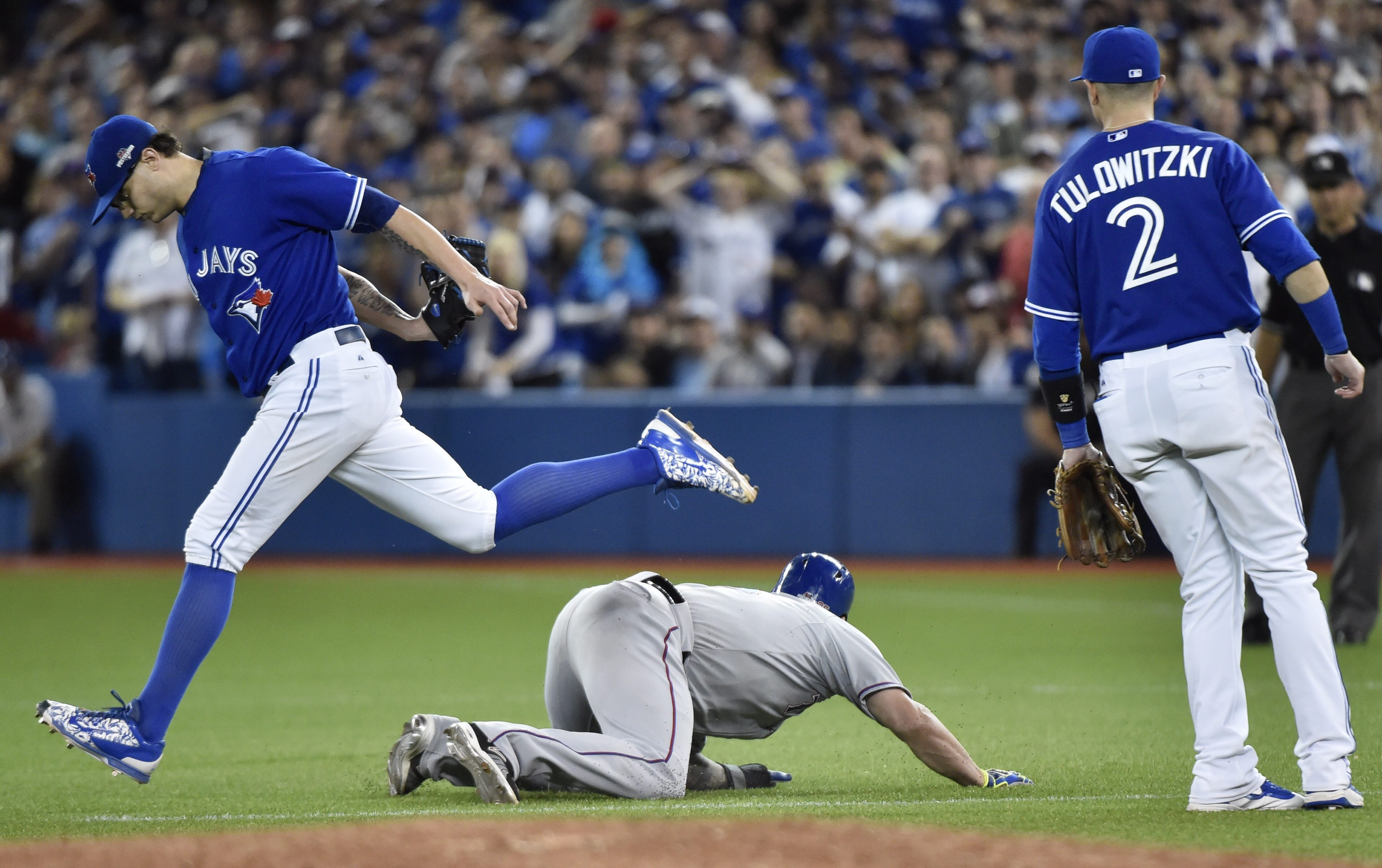 Texas Rangers' Mike Napoli, center, is tagged out by Toronto Blue Jays' Brett Cecil, left, trying to steal second base during the eighth inning in Game 2 of baseballs American League Division Series against the Texas Rangers  in Toronto on Friday, Oct. 9,