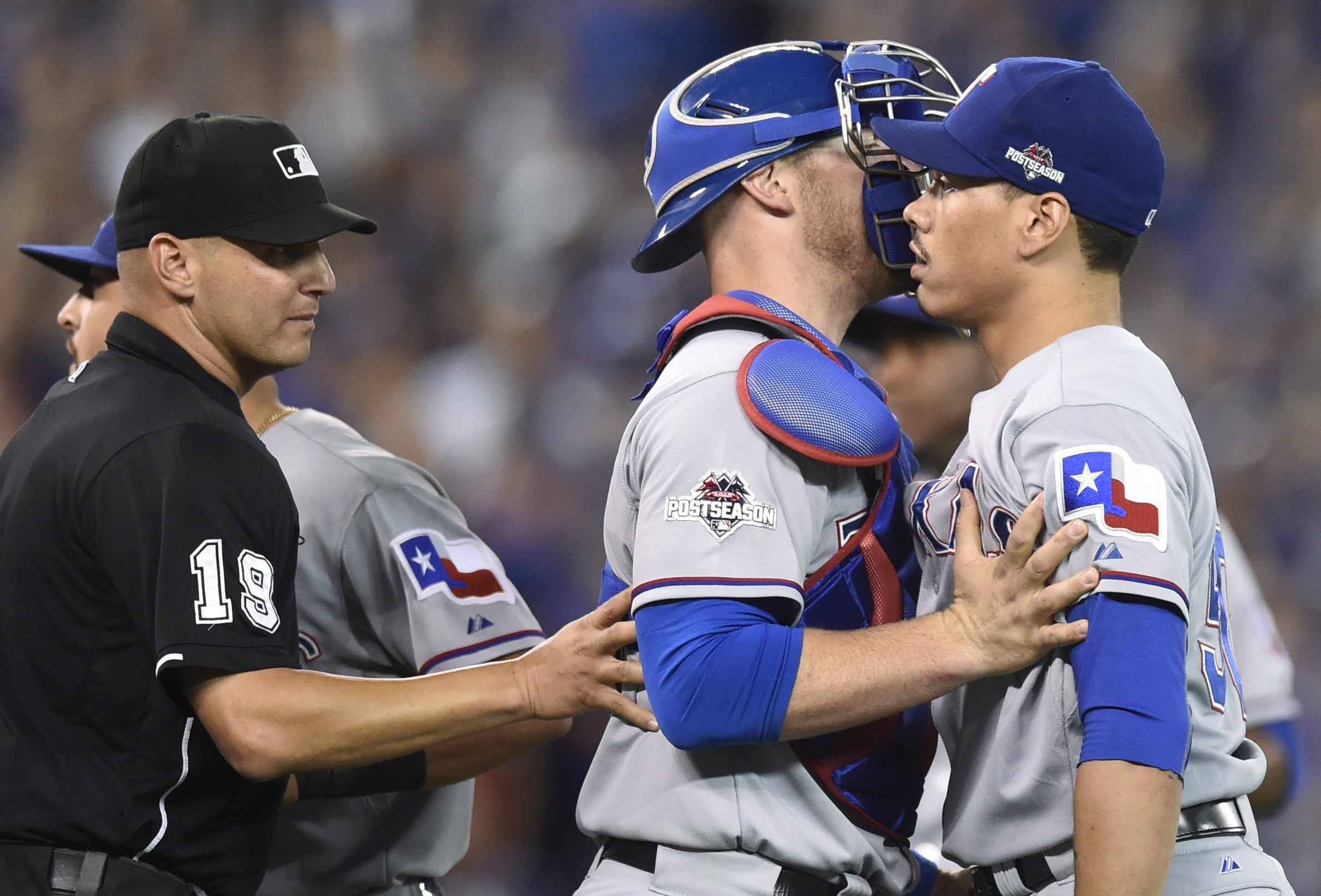 Texas Rangers' Keone Kela, right, is held back by teammate catcher Chris Gimenez, center, during the 13th inning of baseball Game 2 of the American League Division Series against the Toronto Blue Jays in Toronto, Friday, Oct. 9, 2015. (Frank Gunn/The Cana